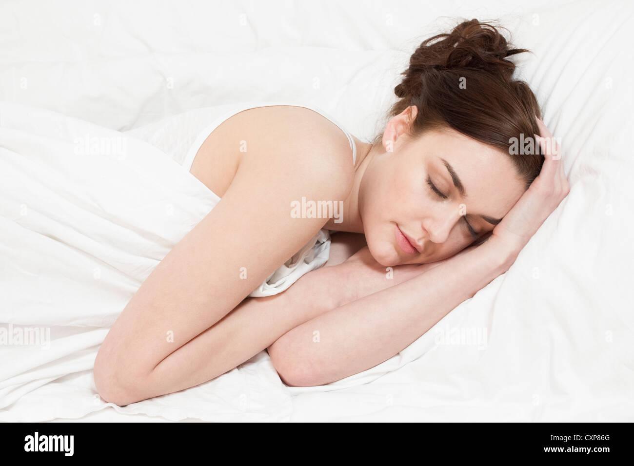 Jeune femme dormir et rêver au lit Photo Stock