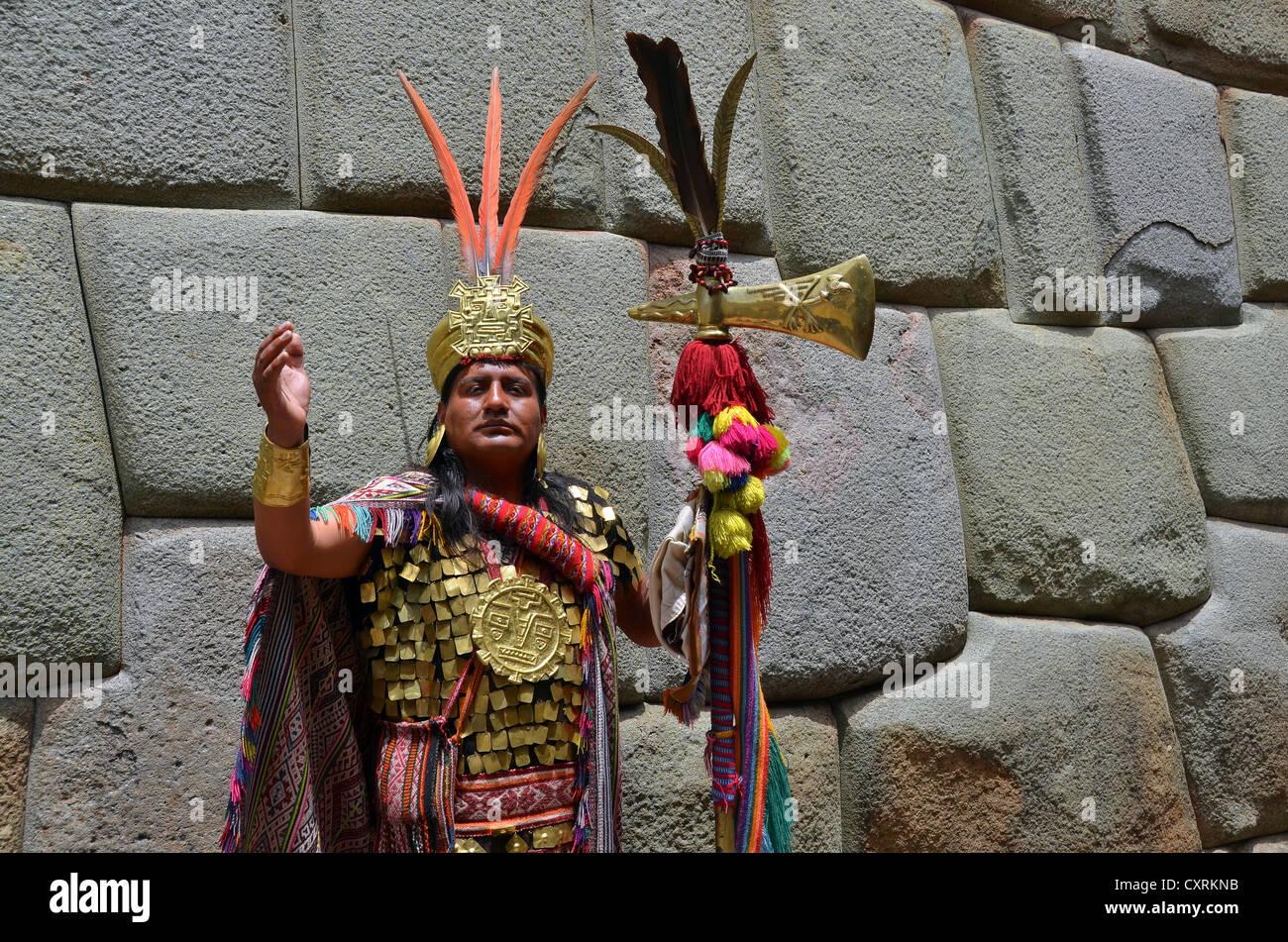 Indio homme habillé comme un chemin inca en face d'un mur antique des incas, centre touristique de Cuzco, Photo Stock