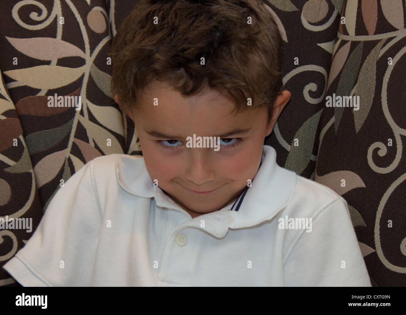 Enfant avec sourire sinistre posing. Photo Stock