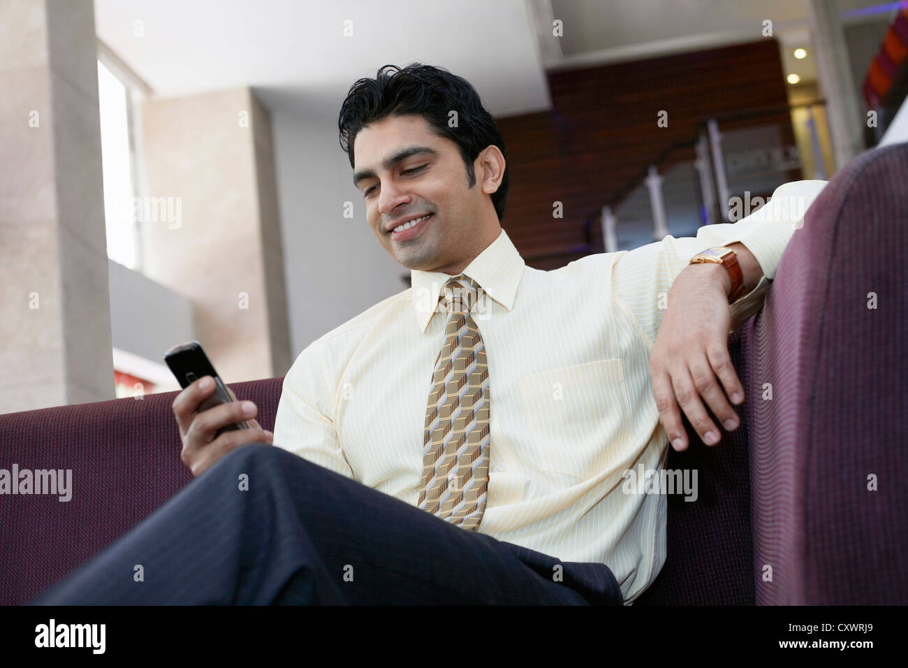 Businessman using cell phone on sofa Banque D'Images