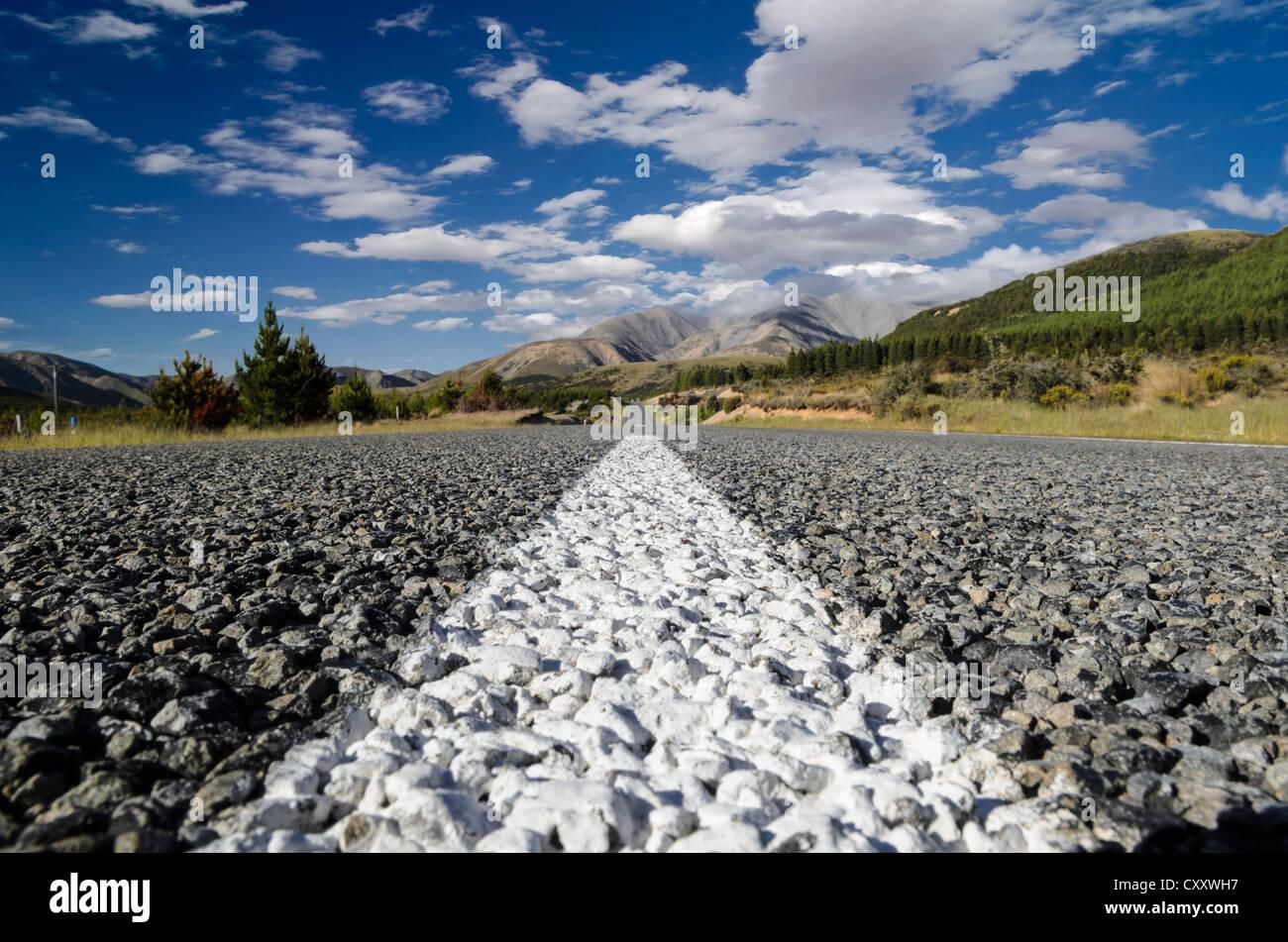 Le marquage blanc sur une route asphaltée à gros, worm's eye view, Arthur's Pass Road, South Island, Photo Stock
