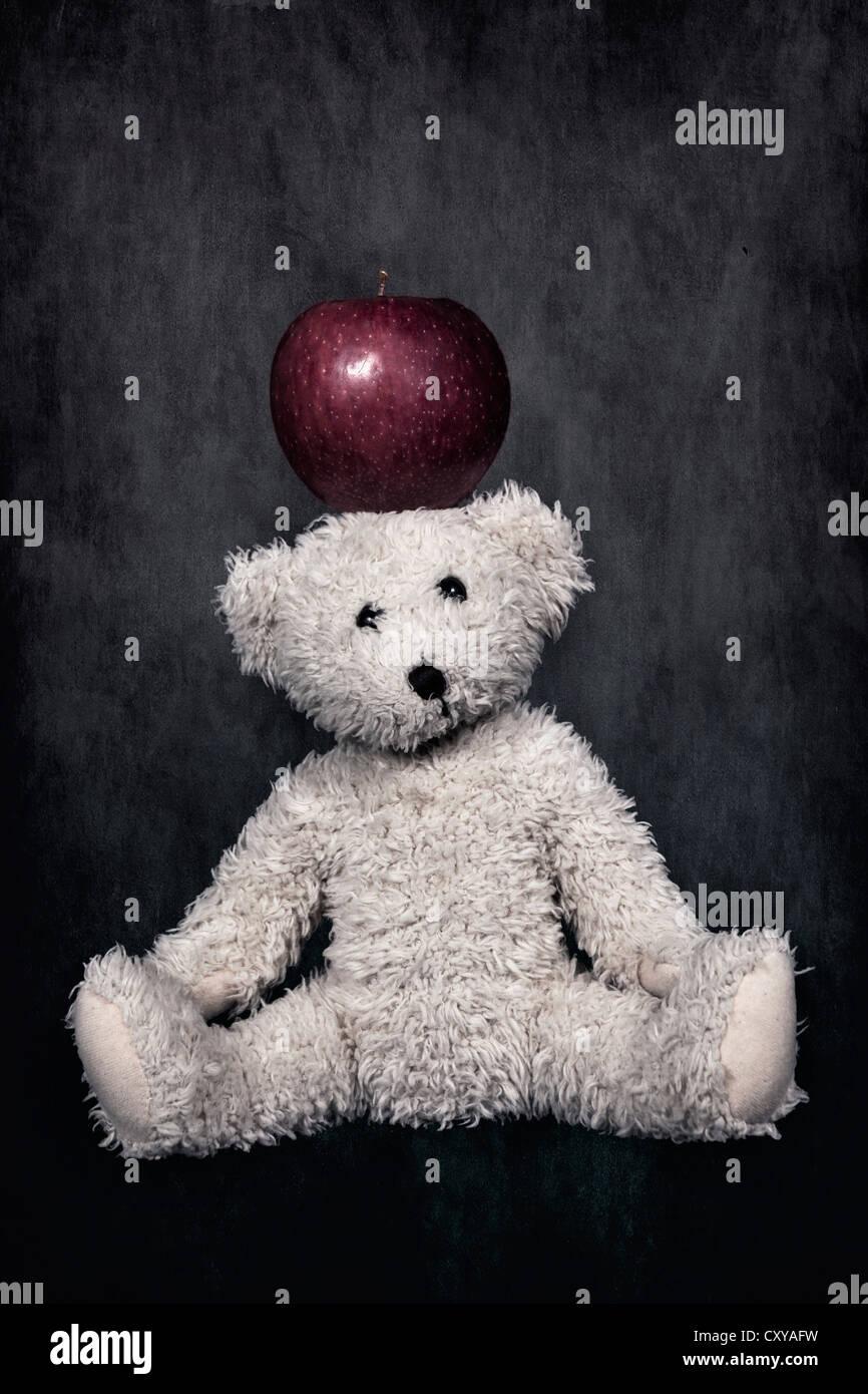 Un ours de nounours blanc avec une pomme rouge sur la tête Photo Stock