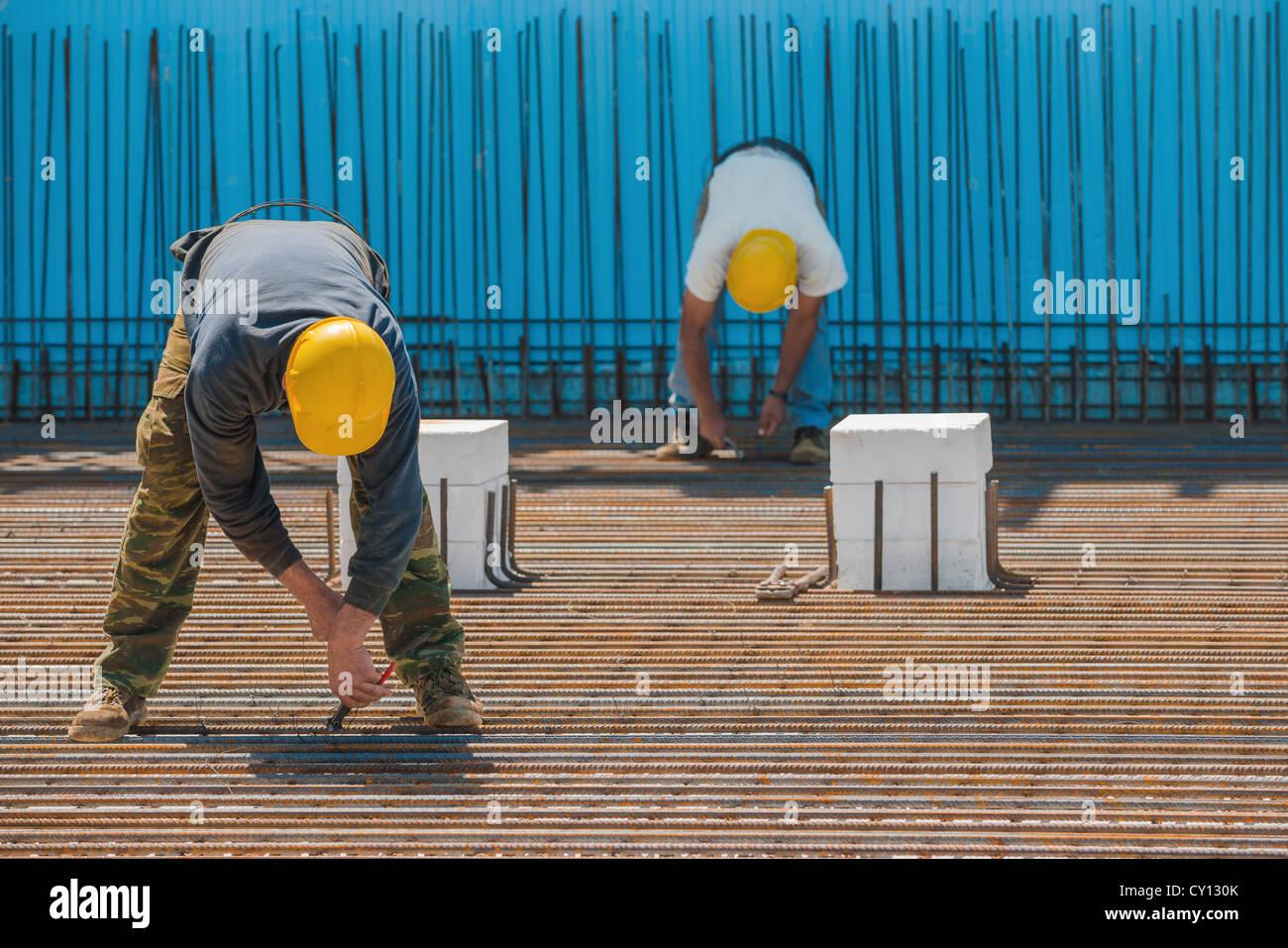 Les travailleurs de la construction l'installation de barres d'acier pour les fils de liaison Photo Stock