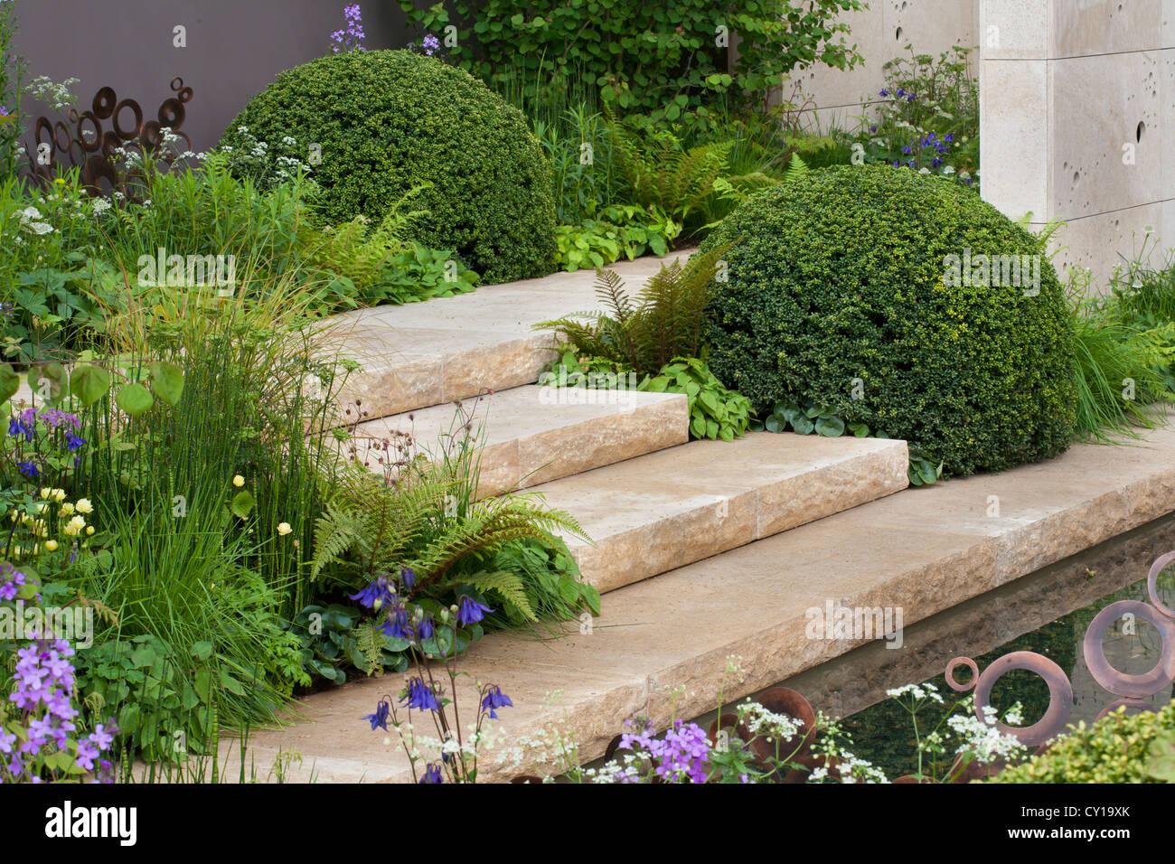 Jardin contemporain conçu avec des arbustes et de l\'eau en forme de ...