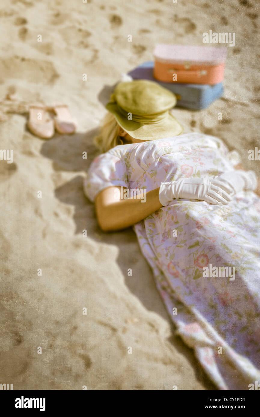 Une femme dans une robe florale est allongé sur une plage à côté de ses  chaussures et deux valises vintage c4dfbc4d2d93