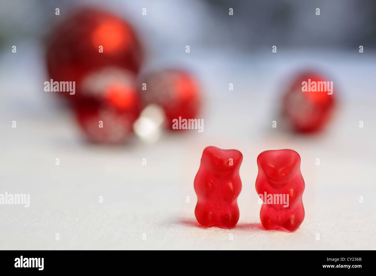 Deux ours gommeux rouge avec des boules rouges sur une nappe blanche Banque D'Images