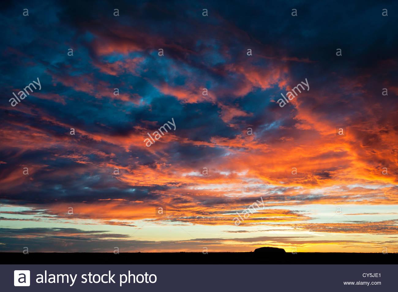 Avec le lever du soleil ardent de la forme noire d'Uluru. Photo Stock