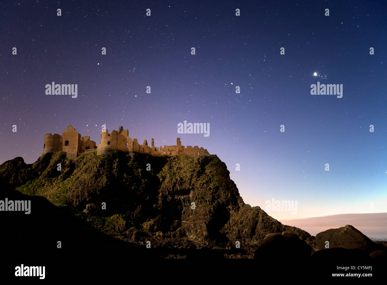 Le Château de Dunluce capturés la nuit par la lune. Photo Stock