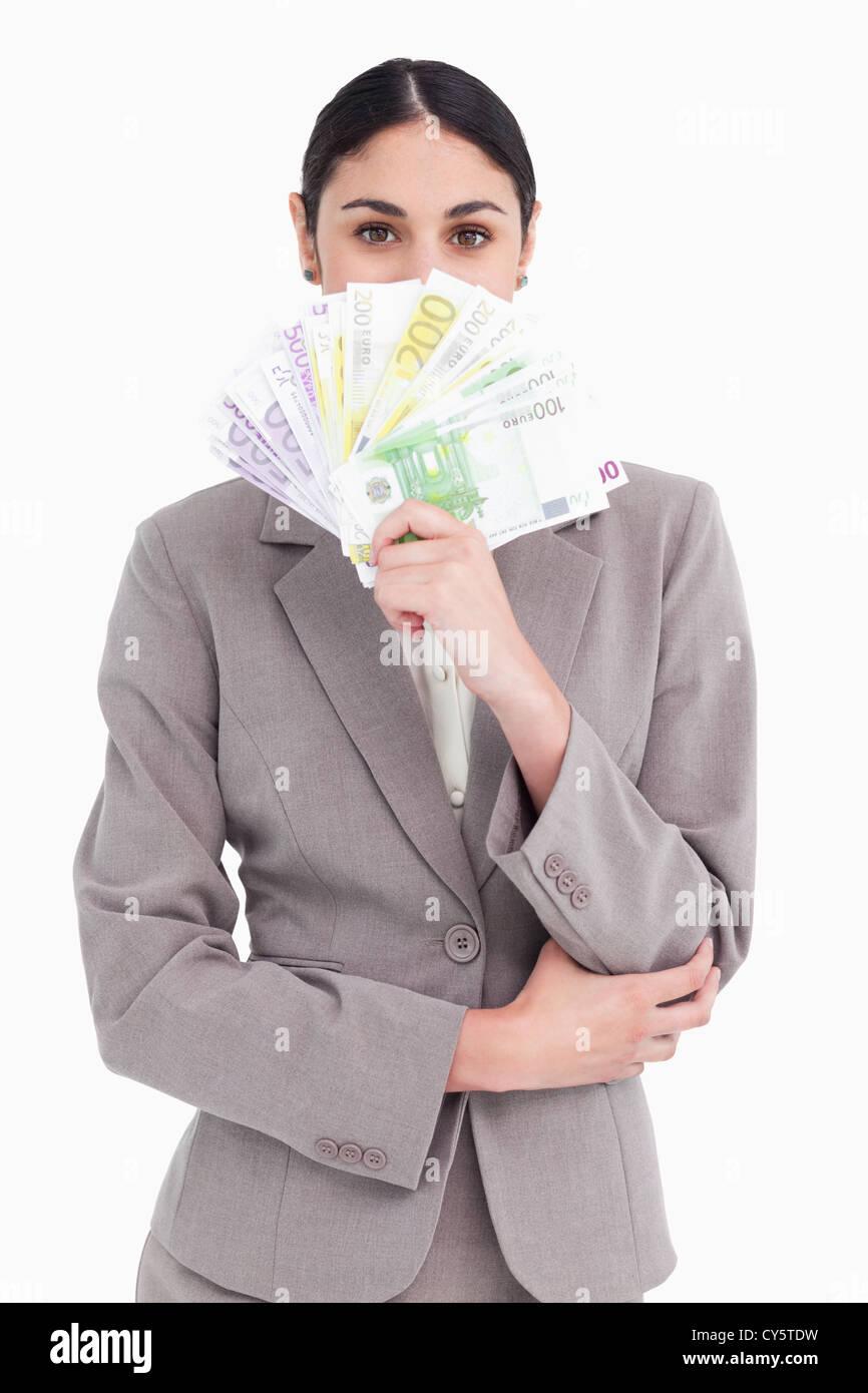 Young businesswoman cachant son visage derrière des billets de banque Banque D'Images