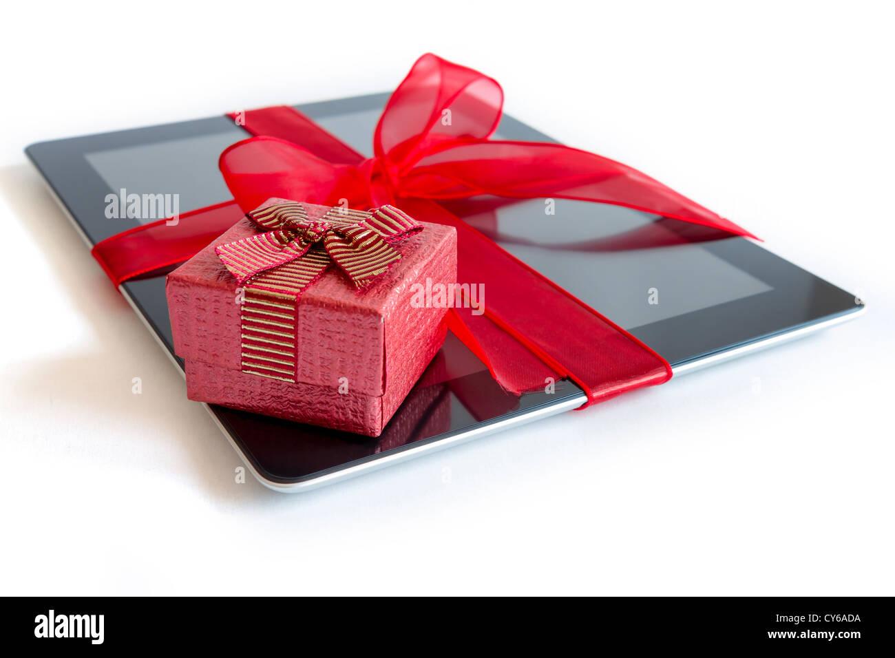 Tablette numérique avec cadeaux ruban rouge isolé sur blanc. Photo Stock