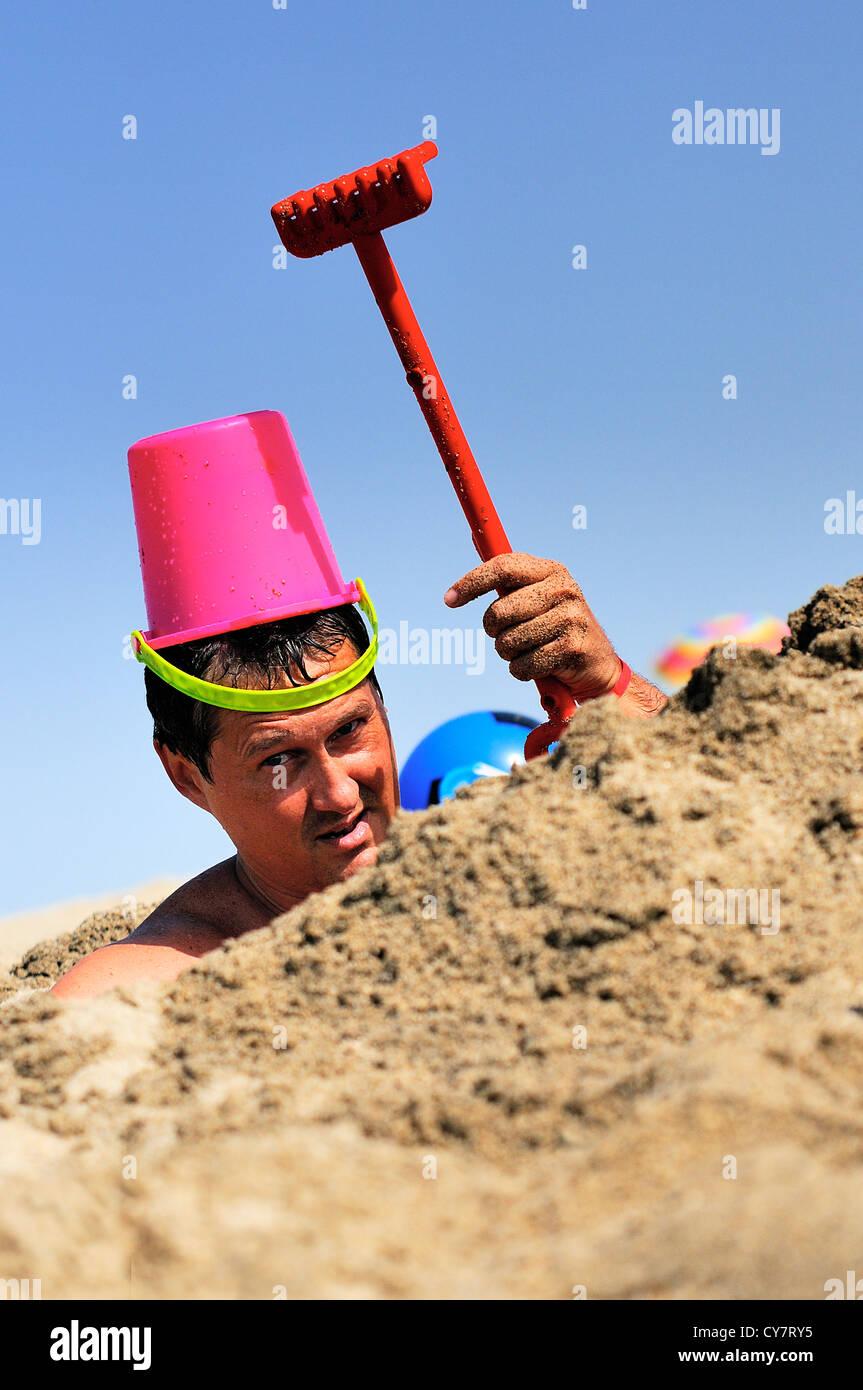 L'homme est fou de plaisanter sur la plage dans le sable avec un râteau et un seau Photo Stock