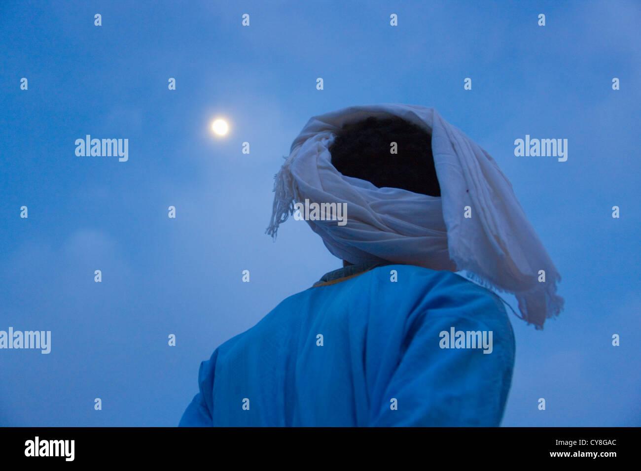 L'homme regardant lune au-dessus du désert du Sahara, l'Erg Chebbi, Maroc Photo Stock