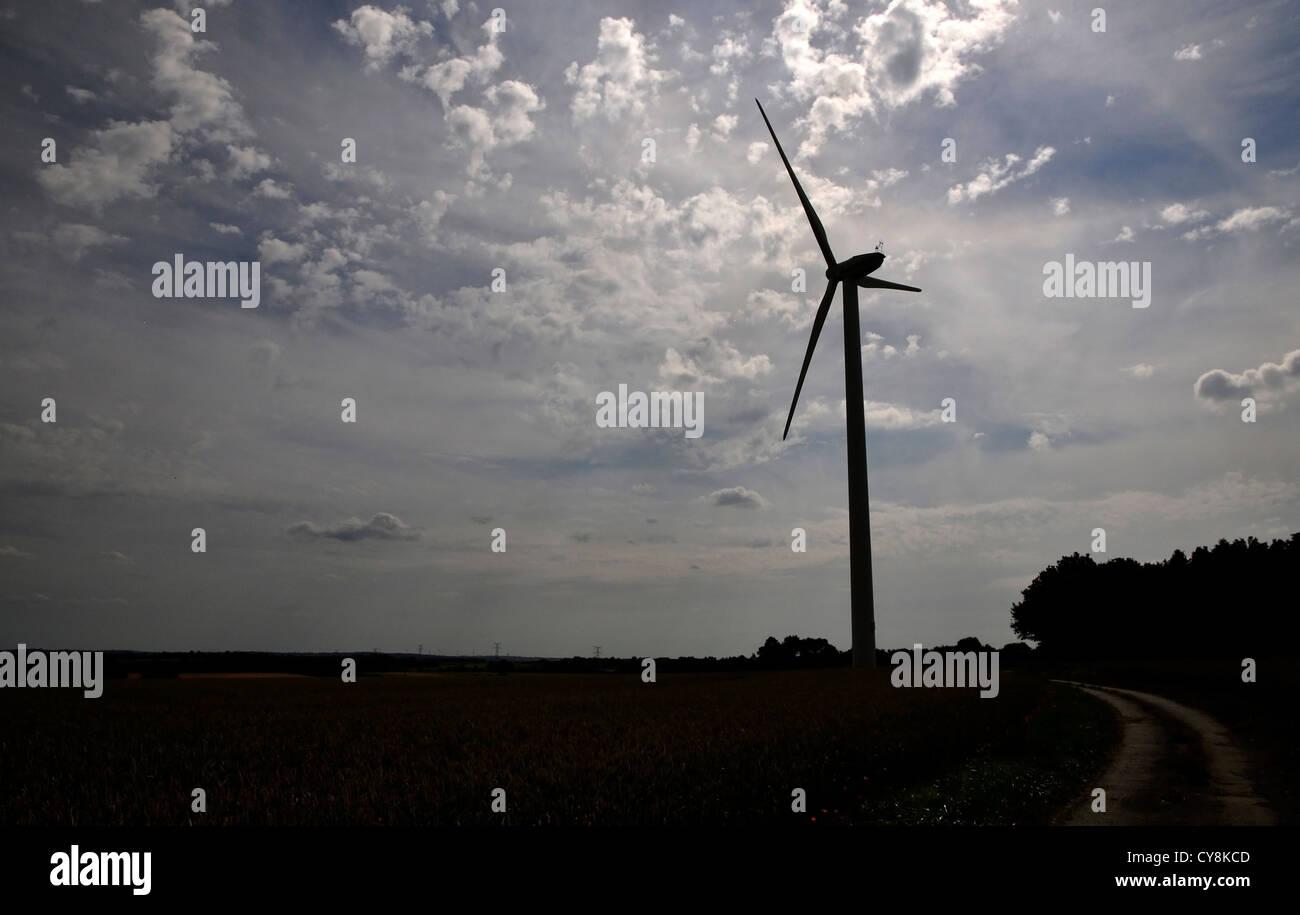 Silhouette d'une éolienne à la campagne avec un ciel nuageux Banque D'Images