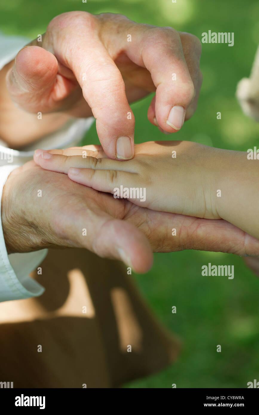 Personnes âgées La main tenant un enfant, cropped Banque D'Images