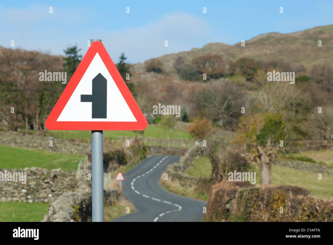 Un panneau routier qui indique une petite route à gauche situé à par une route de campagne sinueuse dans le Lake Banque D'Images