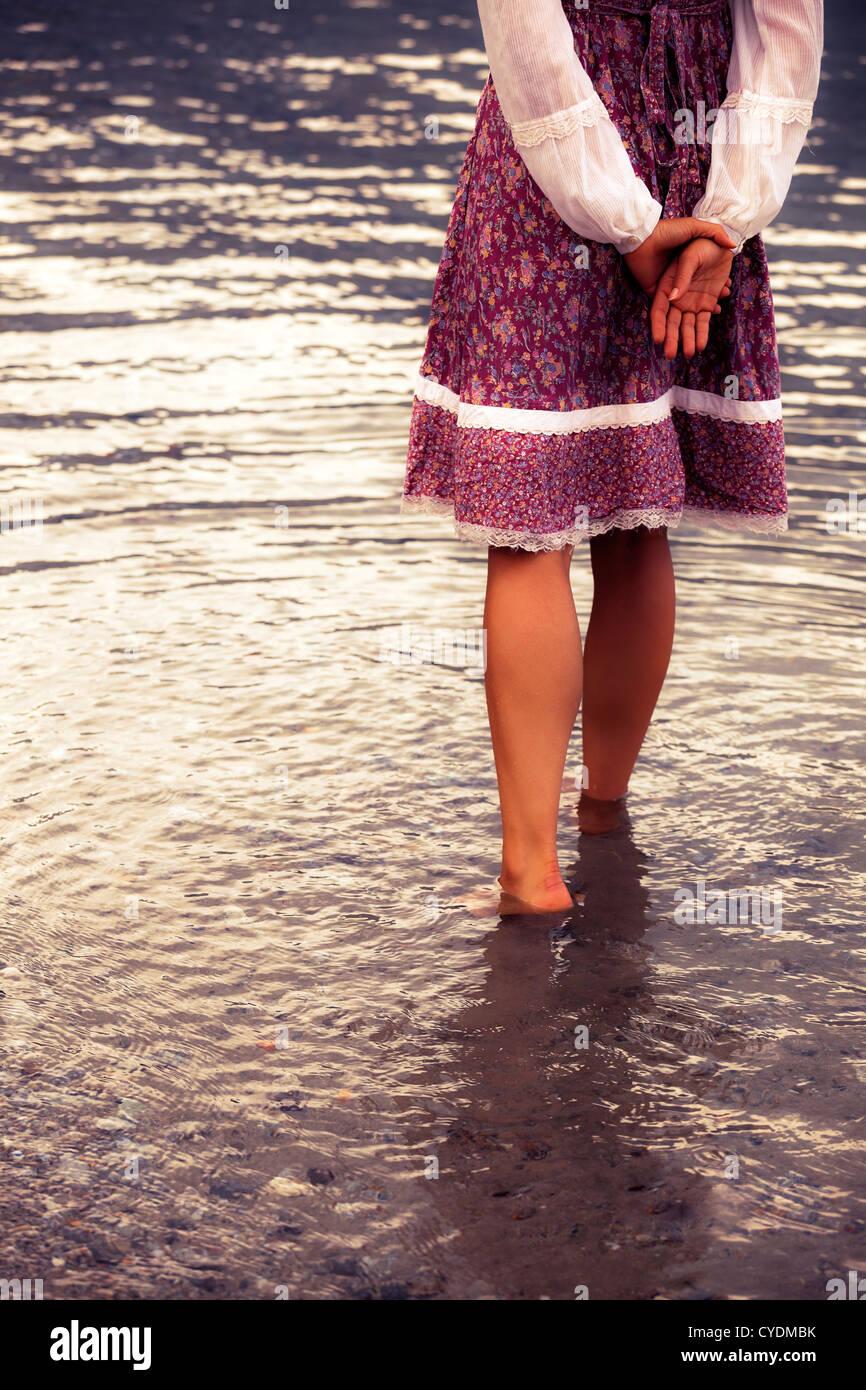 Une fille dans une robe vintage est debout dans l'eau Photo Stock