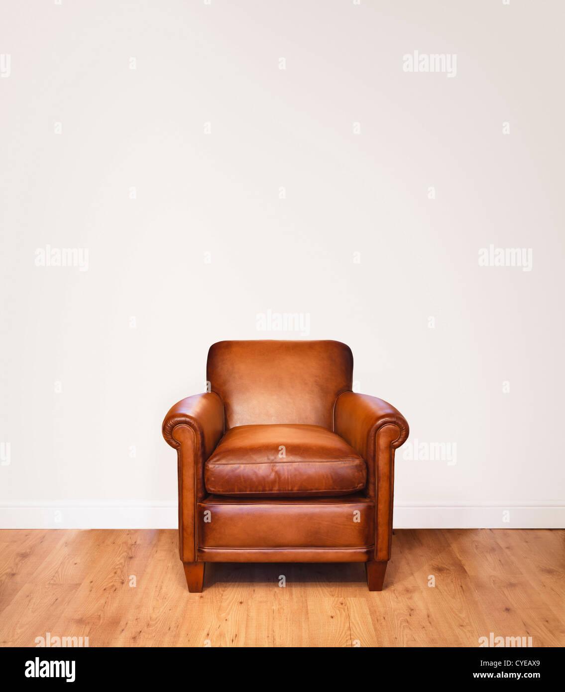 Fauteuil en cuir sur un plancher en bois sur un fond blanc avec beaucoup d'espace pour copier. Le mur a un chemin Photo Stock