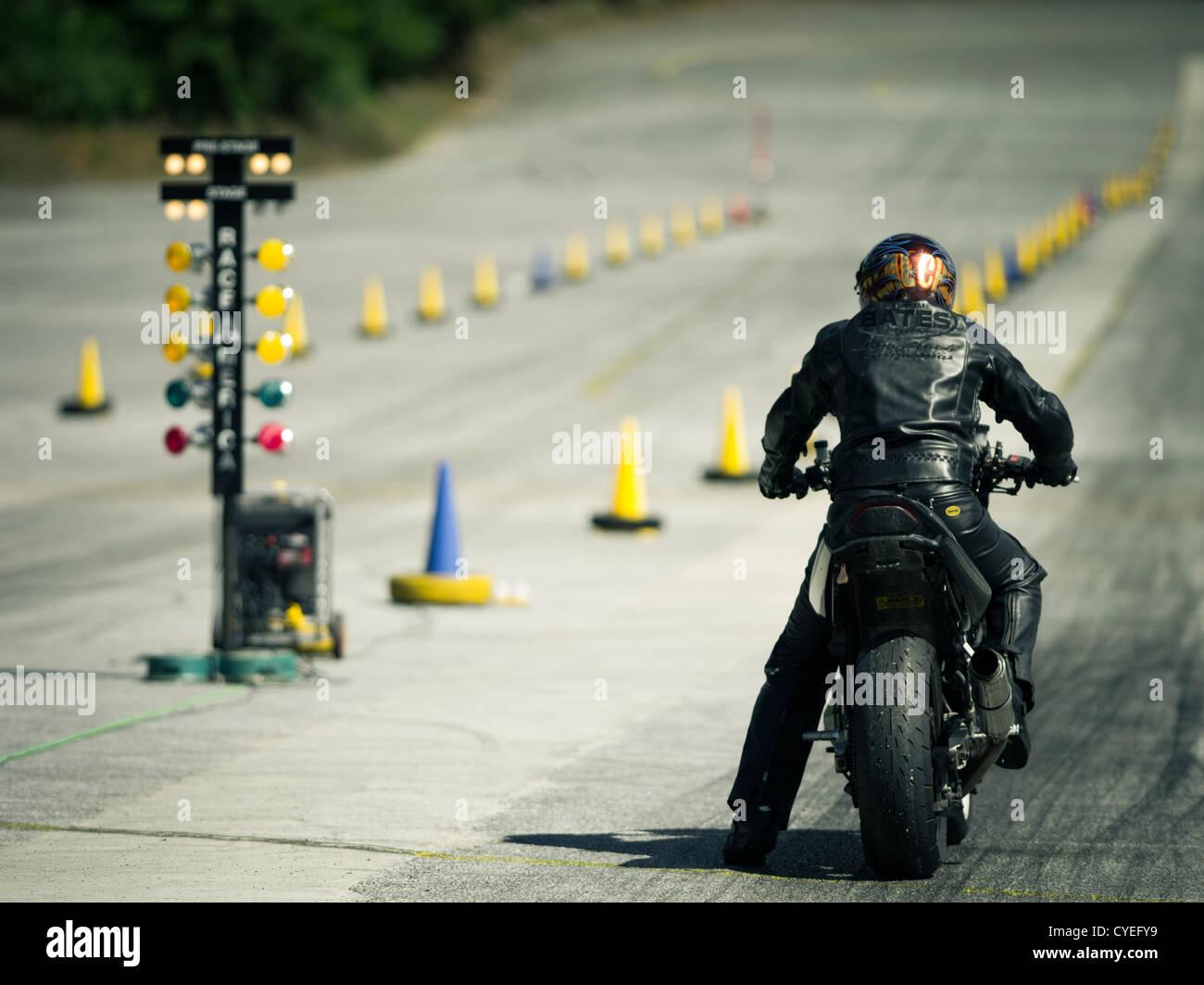 Moto Racer glisser sur le drag strip en attendant le feu vert Photo Stock