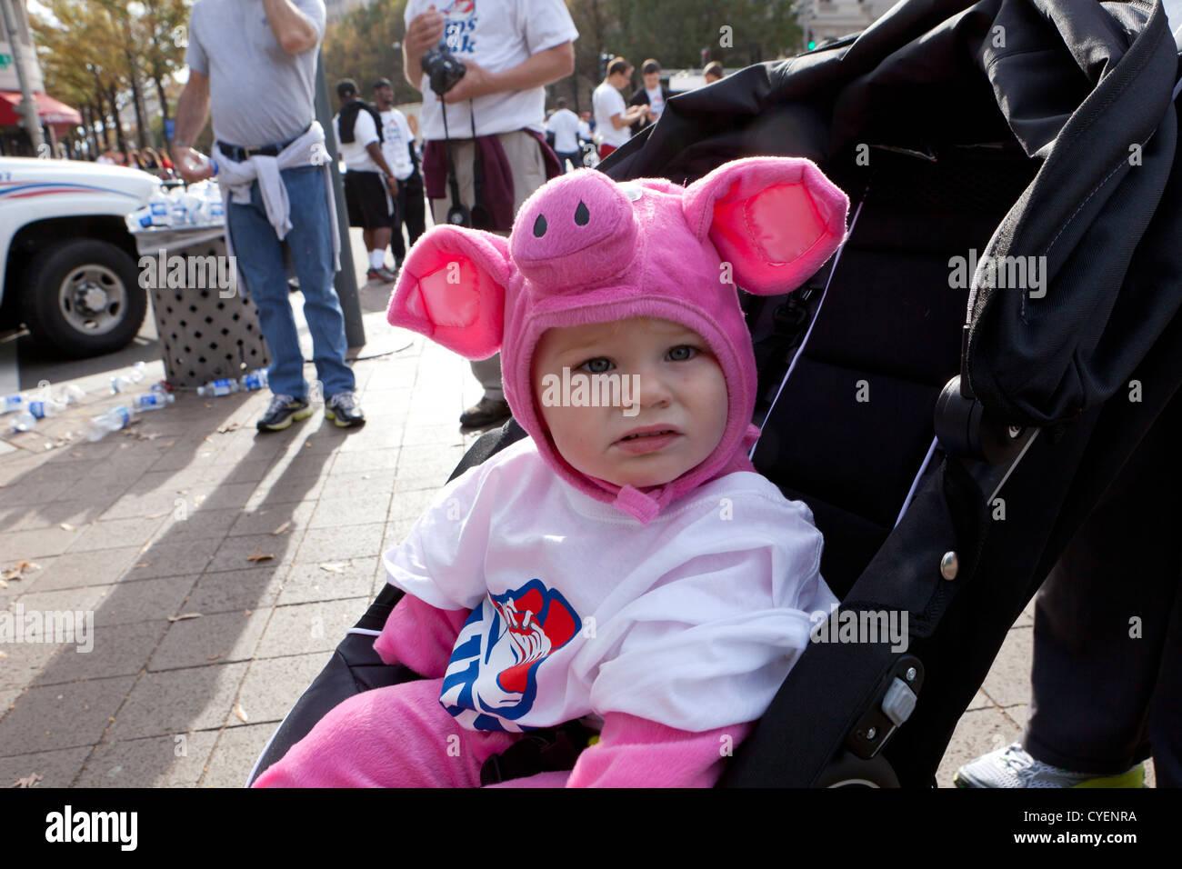 Bébé caucasien habillé en costume cochon assis dans la poussette Photo Stock