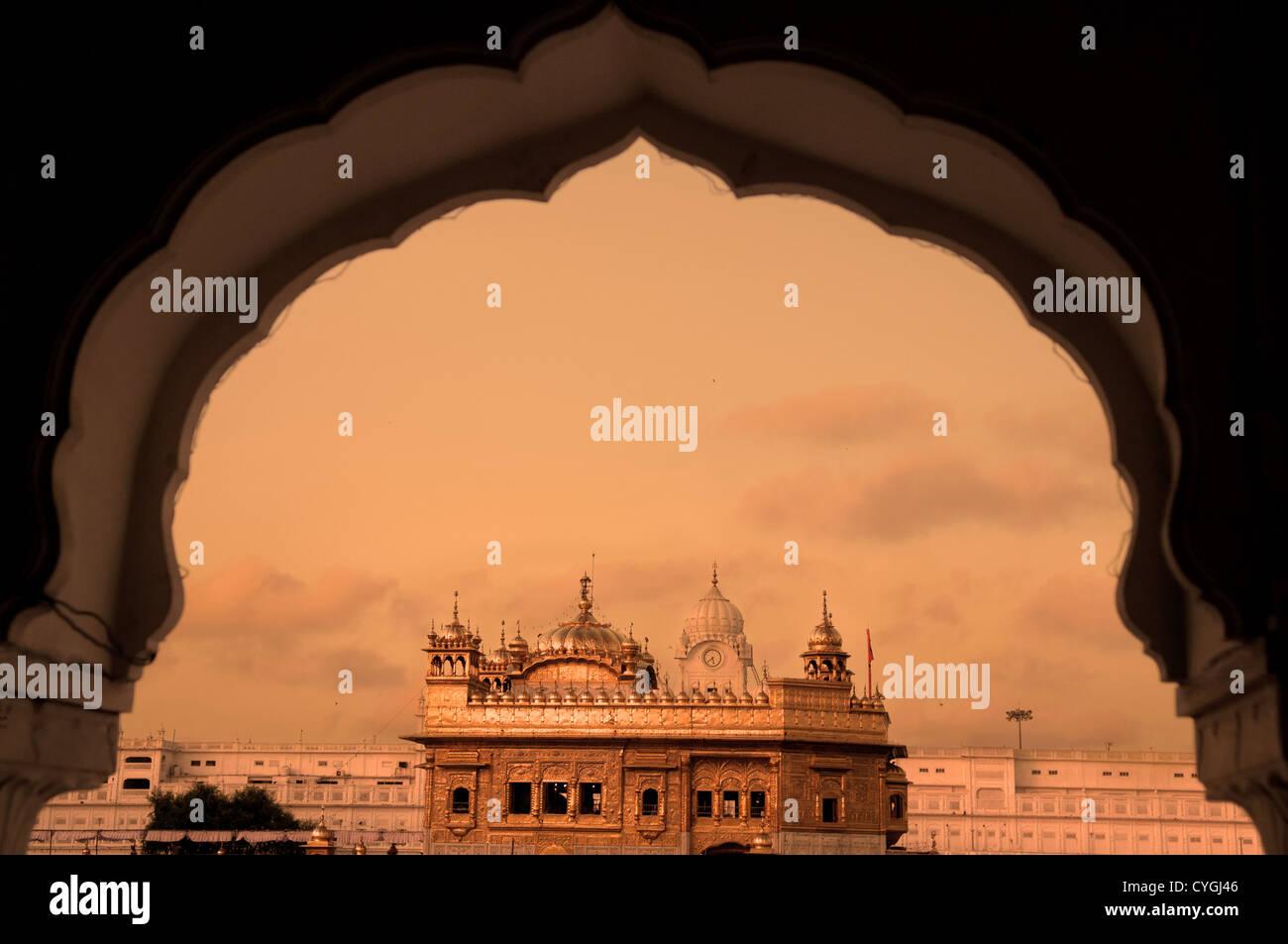 Le Temple d'or d'Amritsar, Inde. Encadrés par des fenêtres de la côté ouest. l'accent Photo Stock