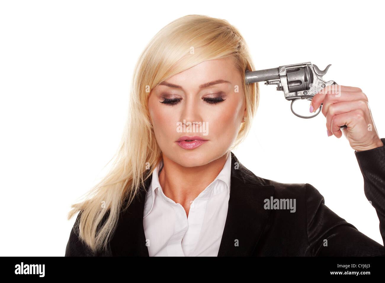 Jeune professionnel femme avec les yeux baissés tenant un pistolet sur sa tête dans une tentative de suicide Photo Stock