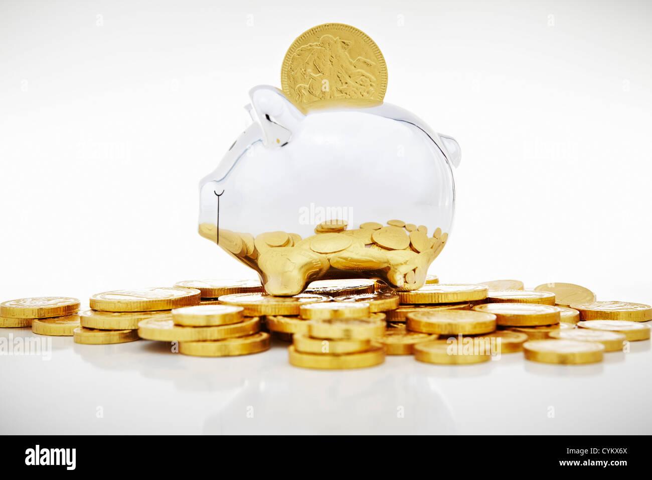 Pile de pièces d'or par piggy bank Photo Stock