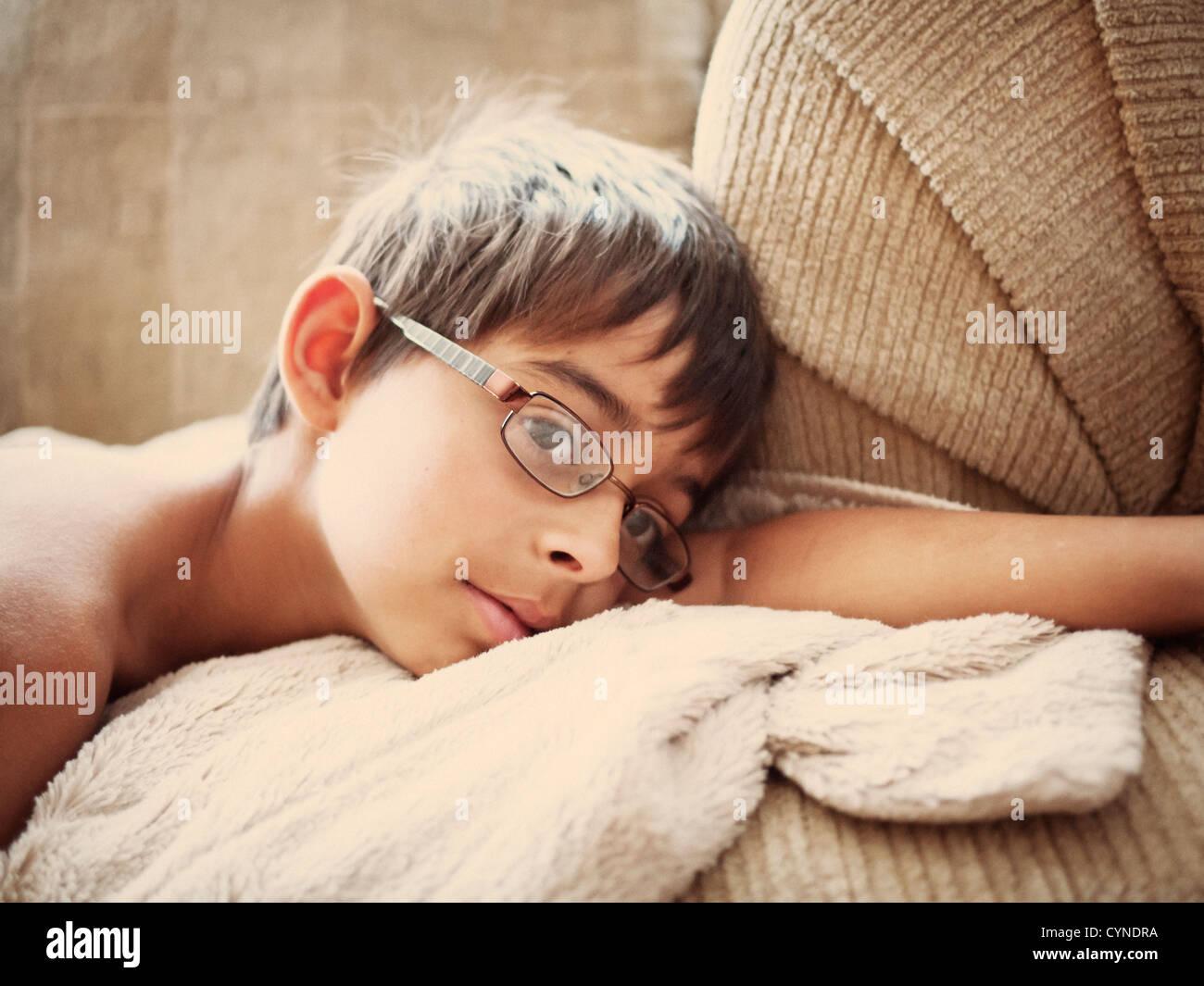 Garçon se trouve sur le canapé le matin tôt. Photo Stock
