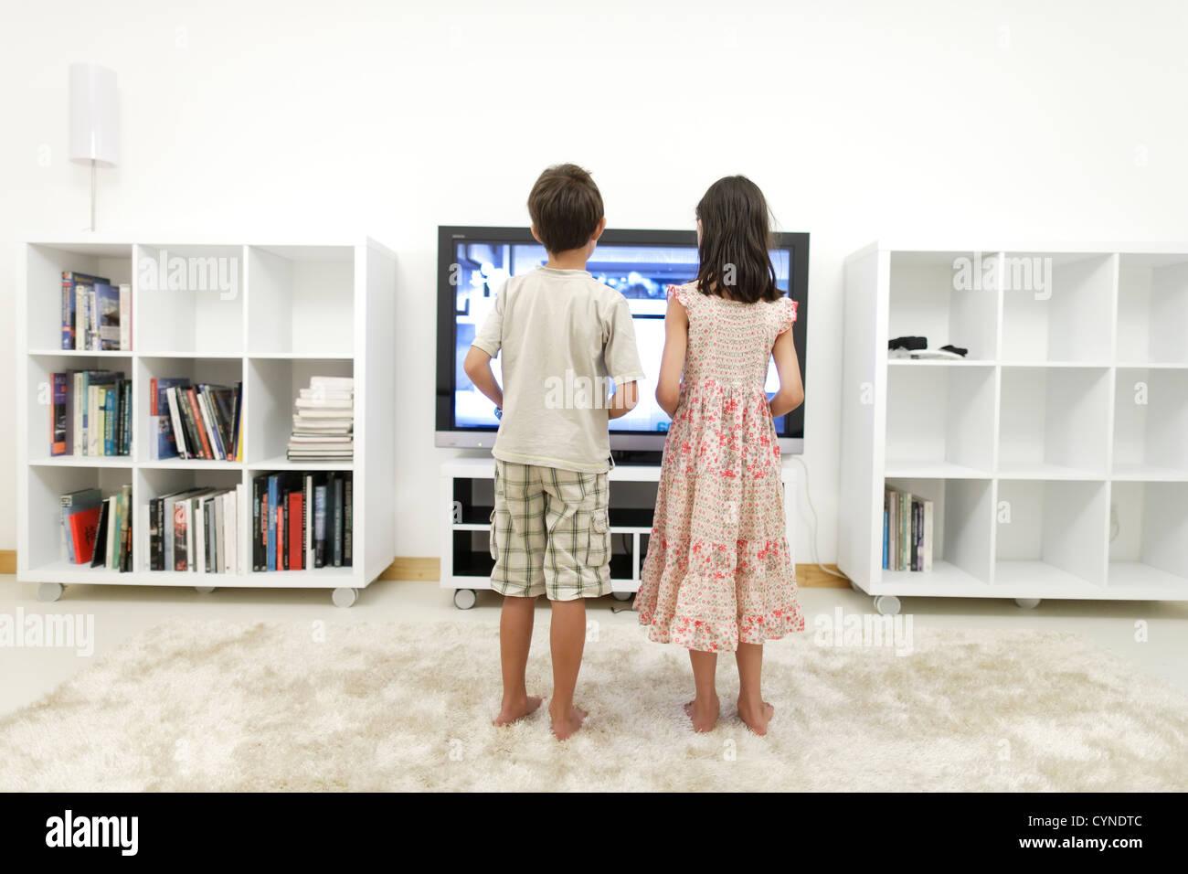 Garçon et fille jouer à des jeux vidéo sur grand écran 55 pouces à la télévision Photo Stock