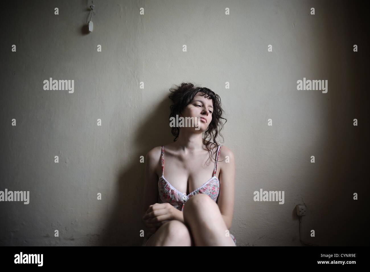 Une tristesse jeune femme est assise dans une salle vide, elle regarder une fenêtre lumineuse Photo Stock