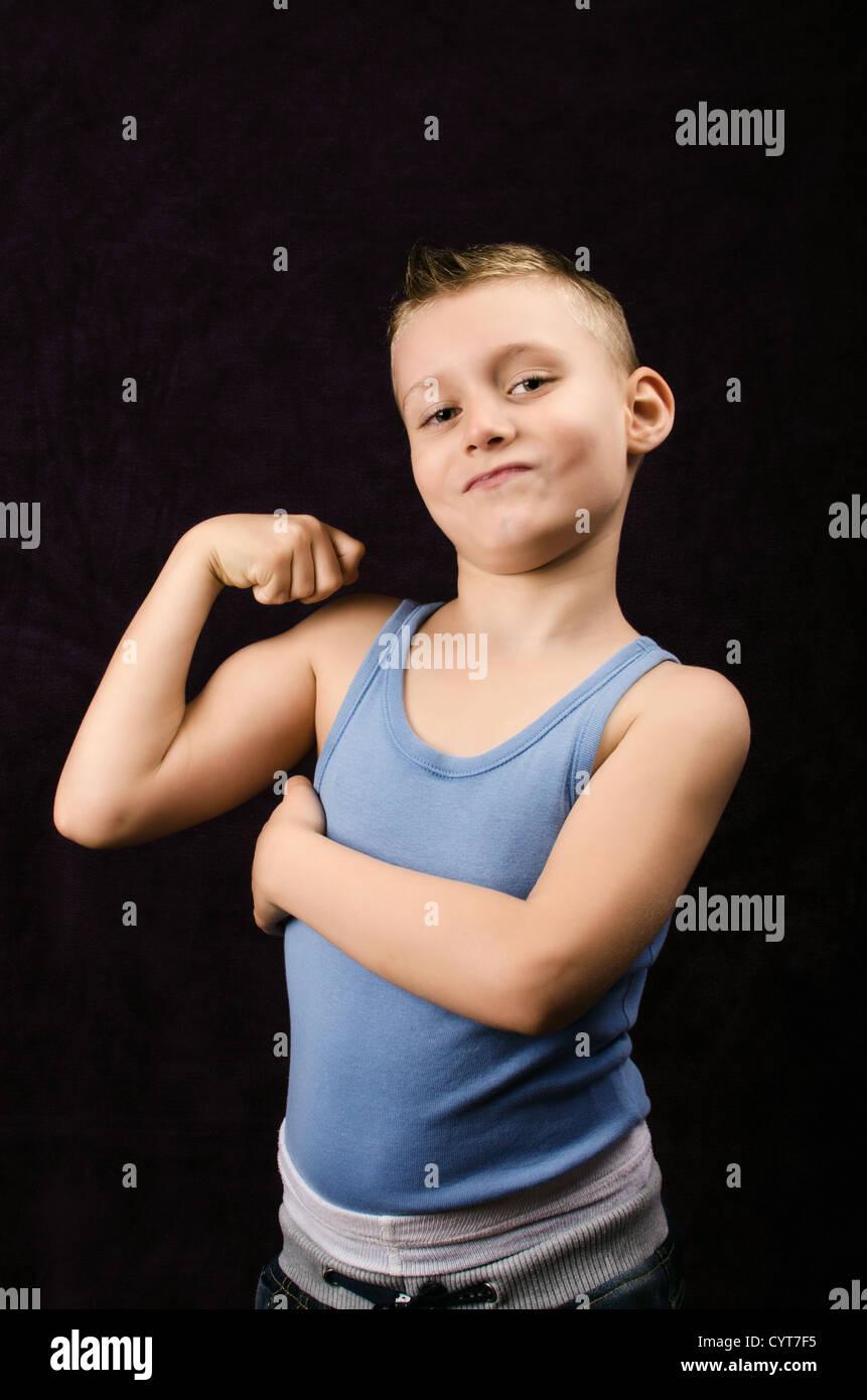 Un jeune garçon exhibant ses muscles sur fond noir Photo Stock