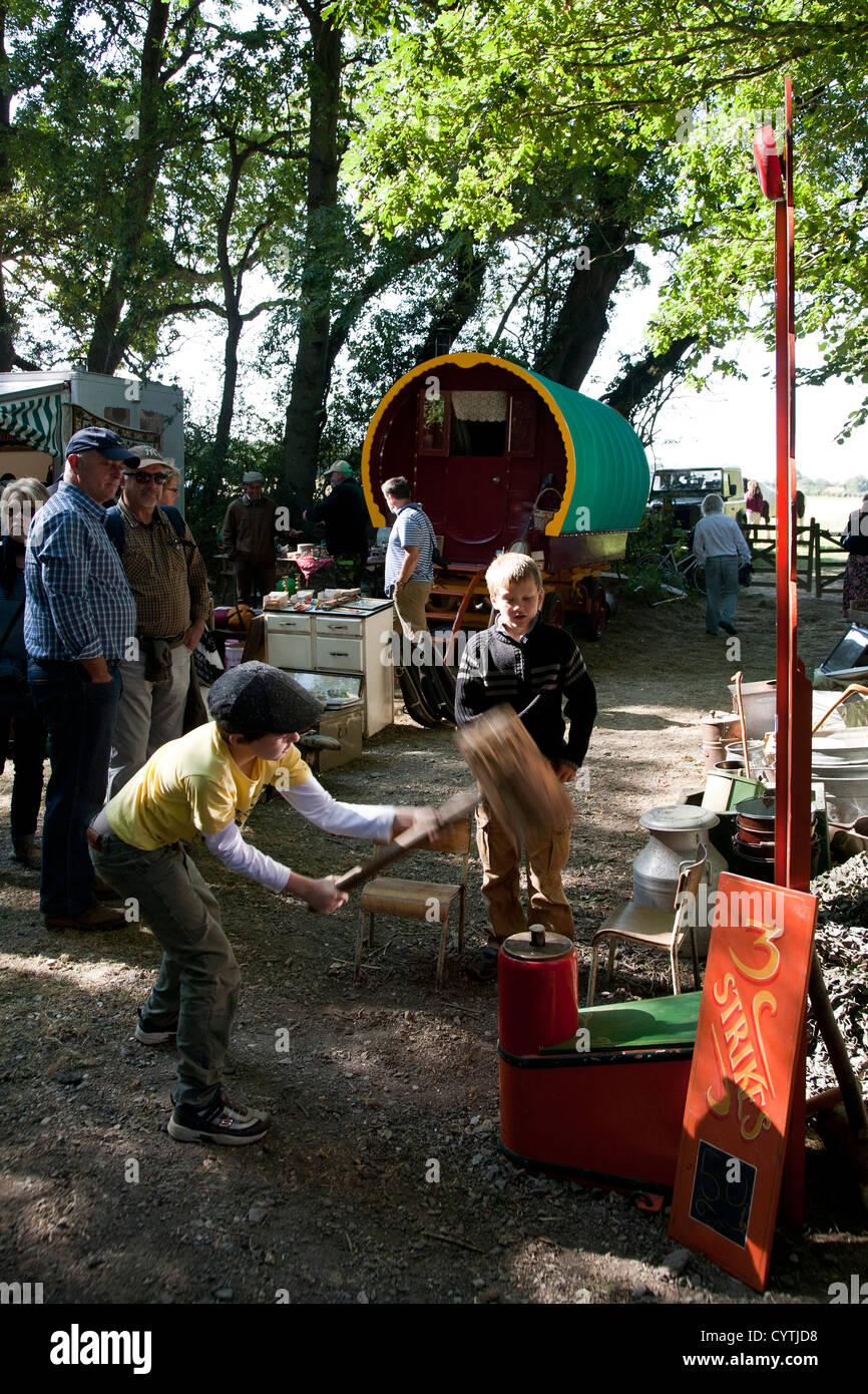 Un garçon balance le marteau vers le bas sur un compteur de puissance Photo Stock