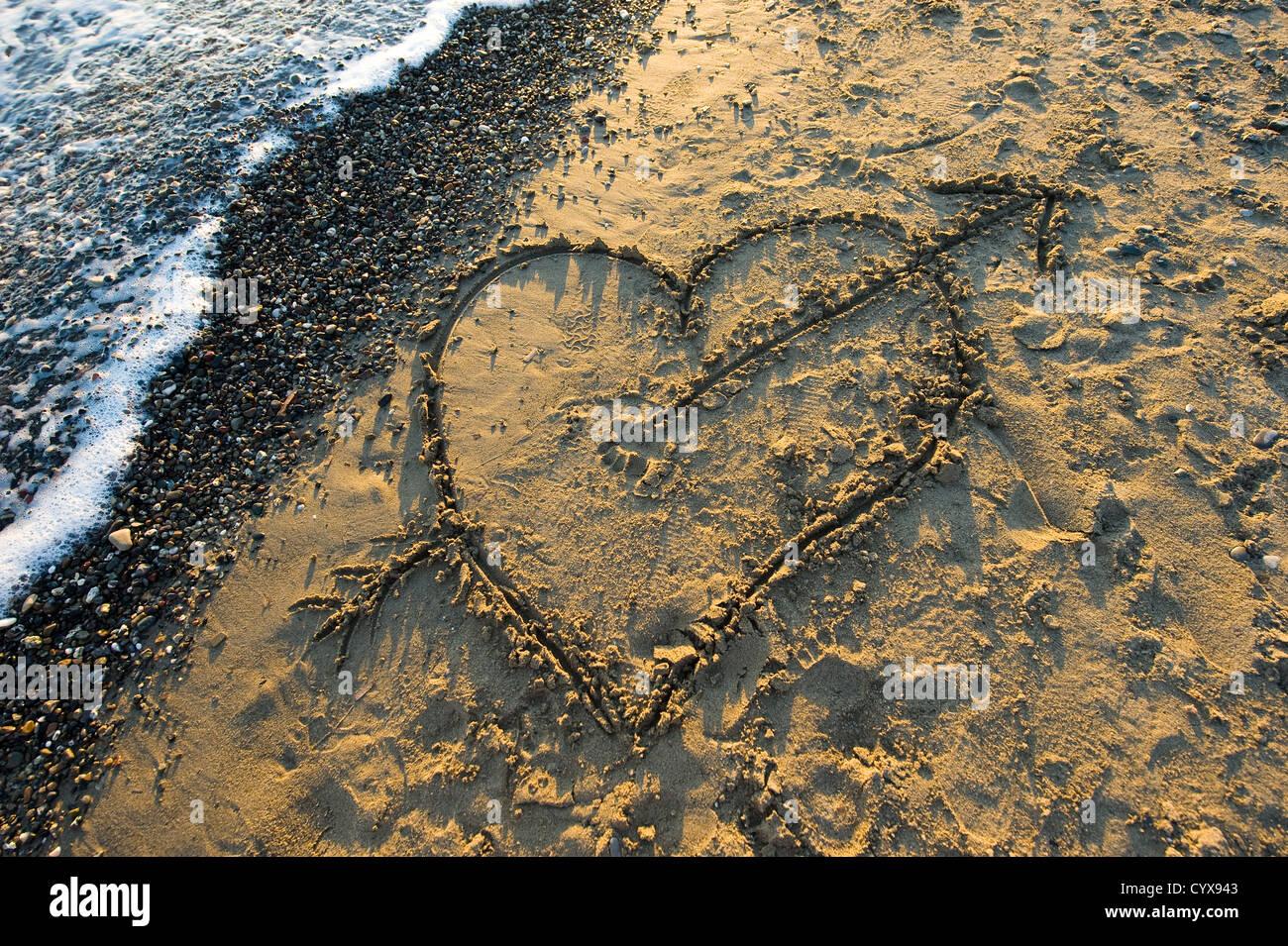 Un coeur avec une flèche tracée dans le sable sur une plage Banque D'Images