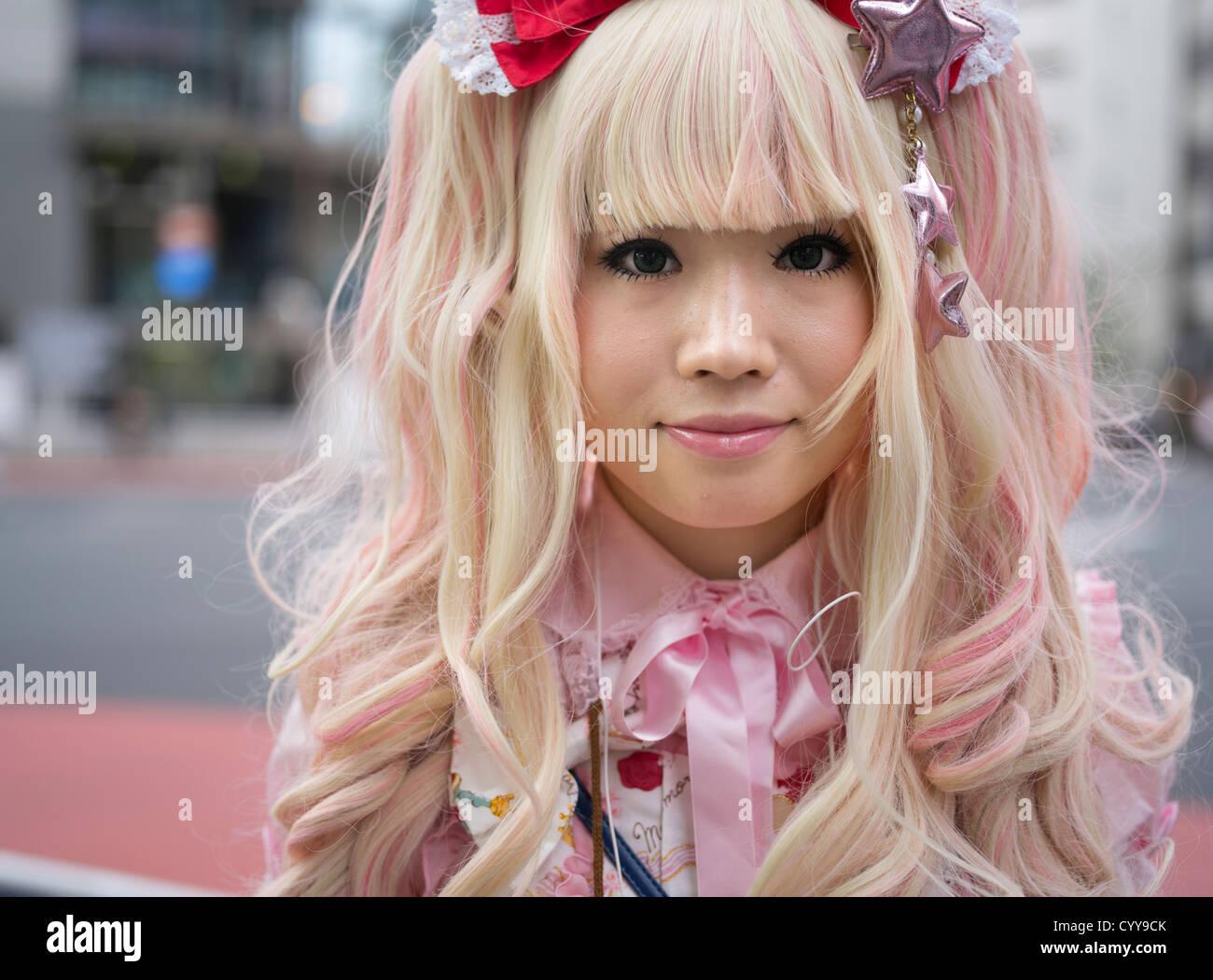 Jeune japonaise en kawaii lolita costume mode alternative avec des cheveux blonds et robe rose Photo Stock
