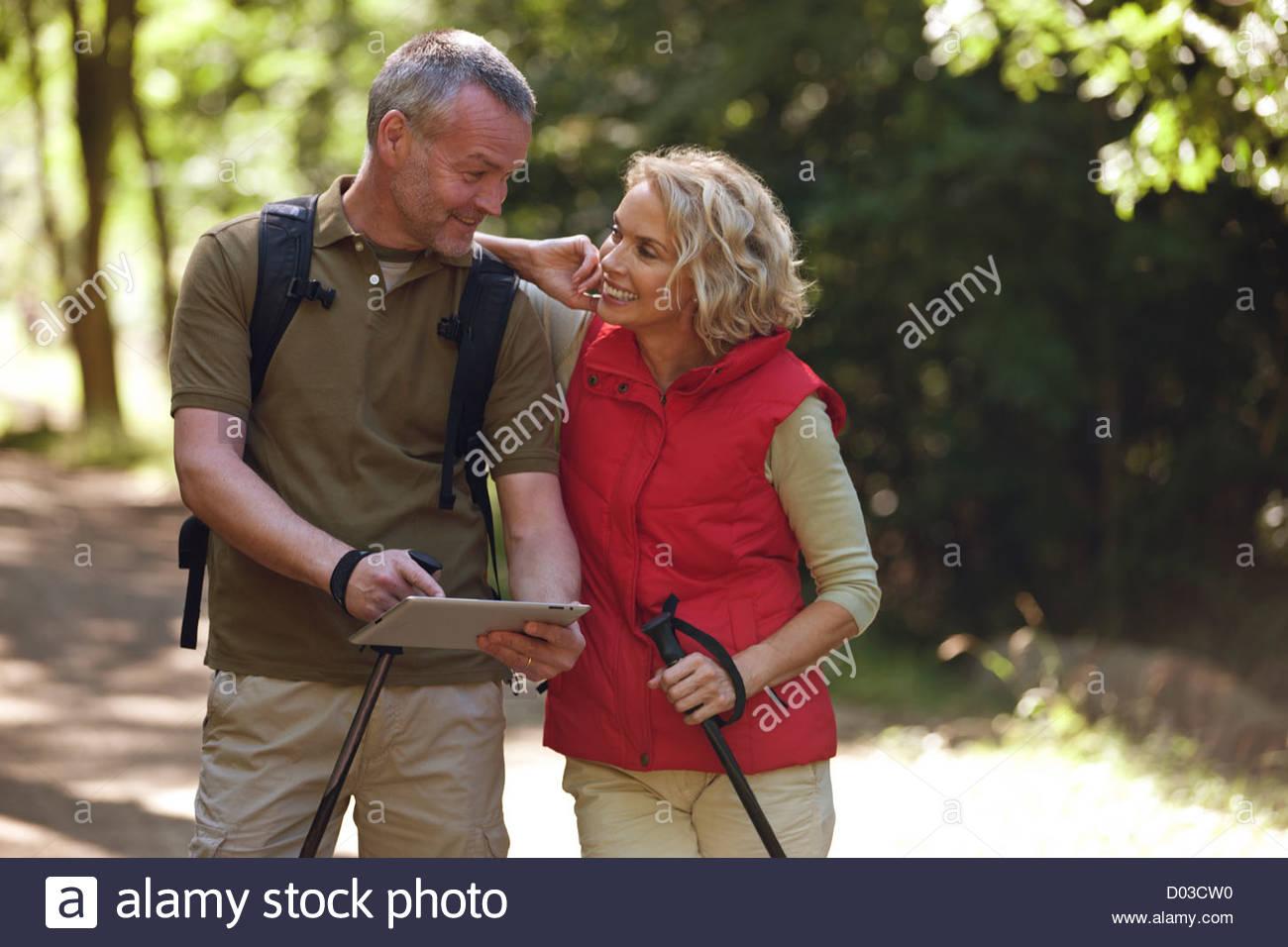 A mature couple marchant sur un chemin de pays, la navigation avec un ordinateur tablette Photo Stock