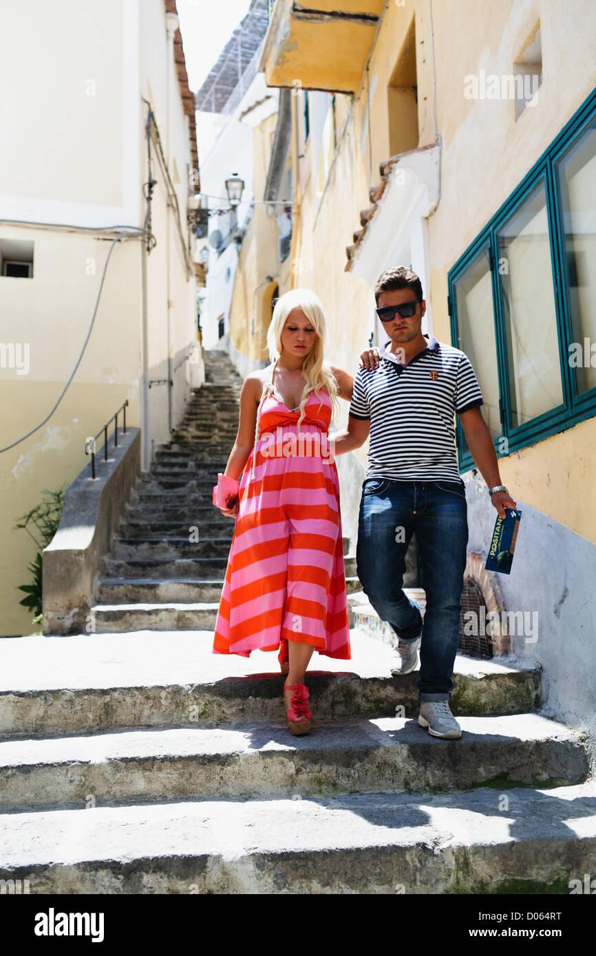 Jeune couple en train de marcher vers le bas de l'escalier dans une rue étroite, Positano, Campanie, Italie Photo Stock