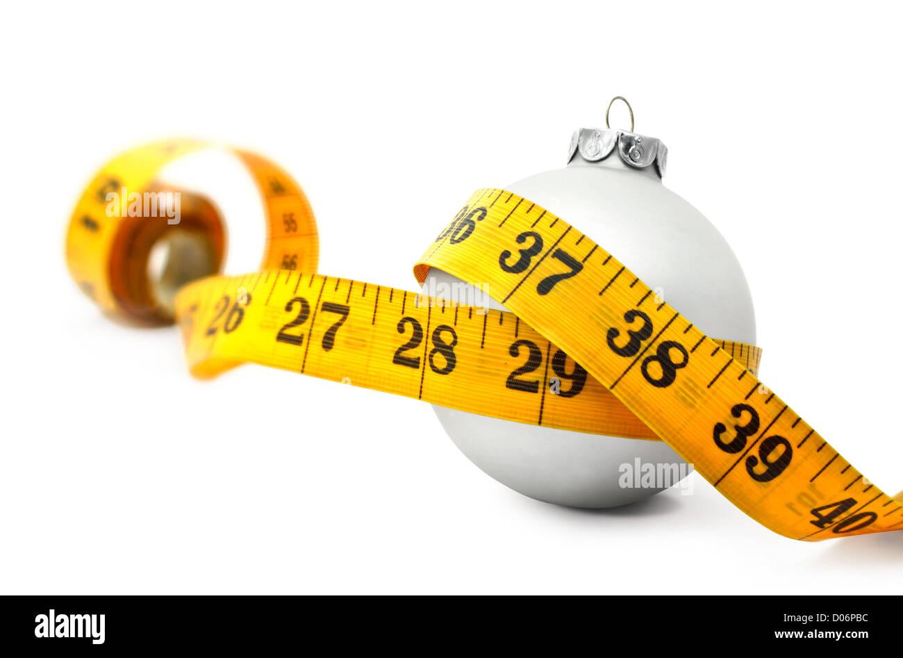 Ruban de mesure autour d'un concept babiole Noël symbolisant le gain de poids en mangeant trop de nourriture. Photo Stock