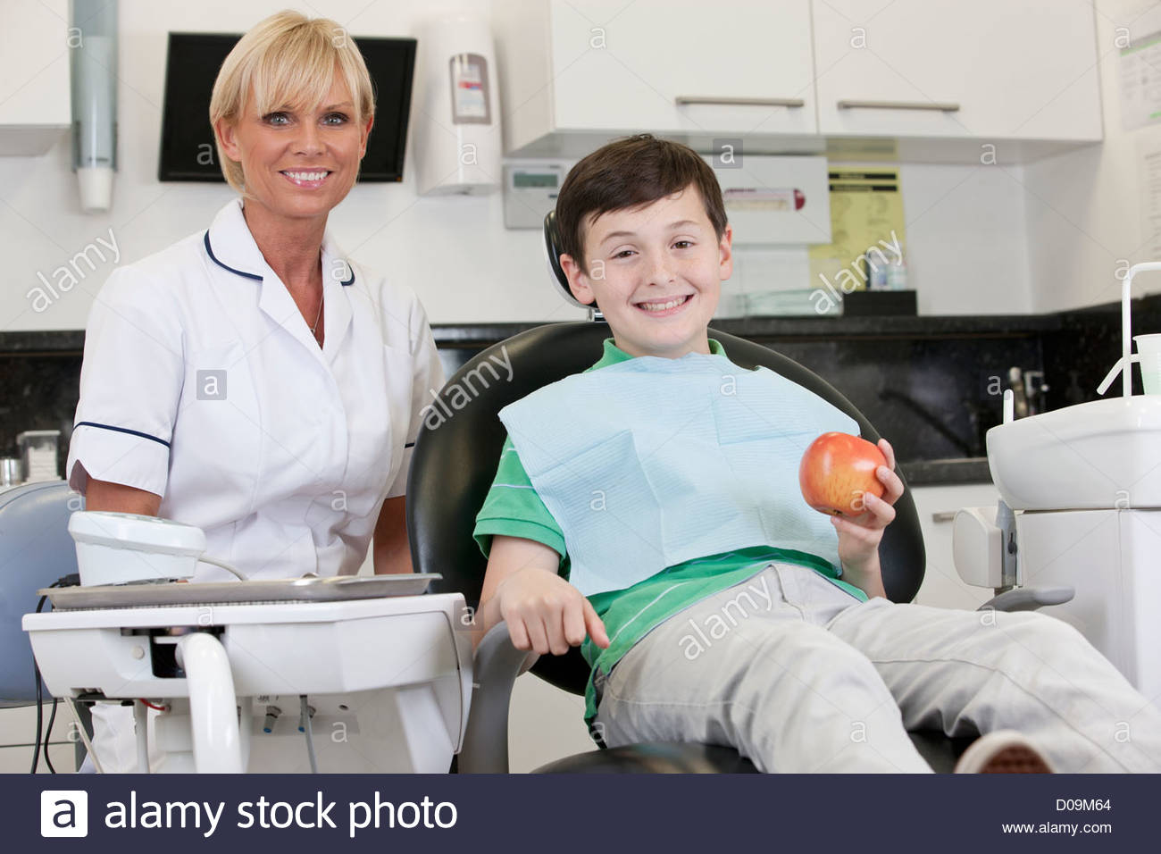 Un jeune garçon chez le dentiste holding an apple Photo Stock