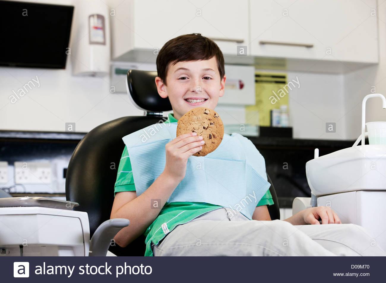Un jeune garçon chez le dentiste tenant un cookie géant Photo Stock