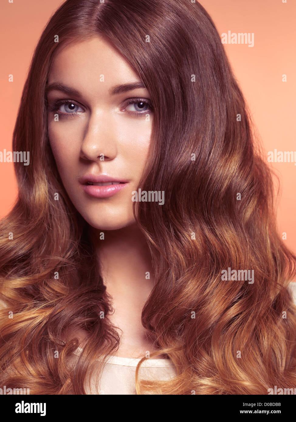 Portrait de beauté d'une jeune femme aux longs cheveux bruns ondulés Photo Stock