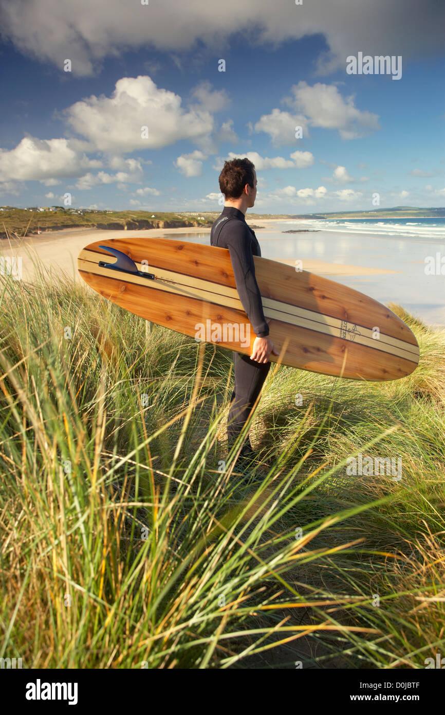 Un homme debout avec son surfboard at Godrevy Point. Banque D'Images