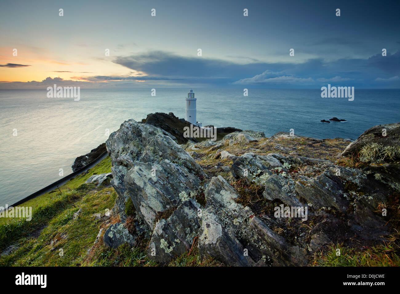 Aube lumière bleu d'encre sur la baie de début et le phare sur la côte sud du Devon. Photo Stock