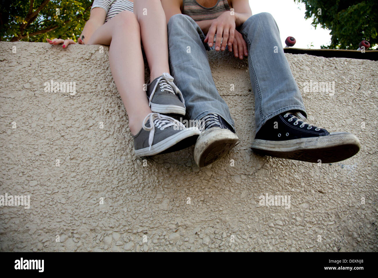 Young couple sitting on wall, low section Photo Stock