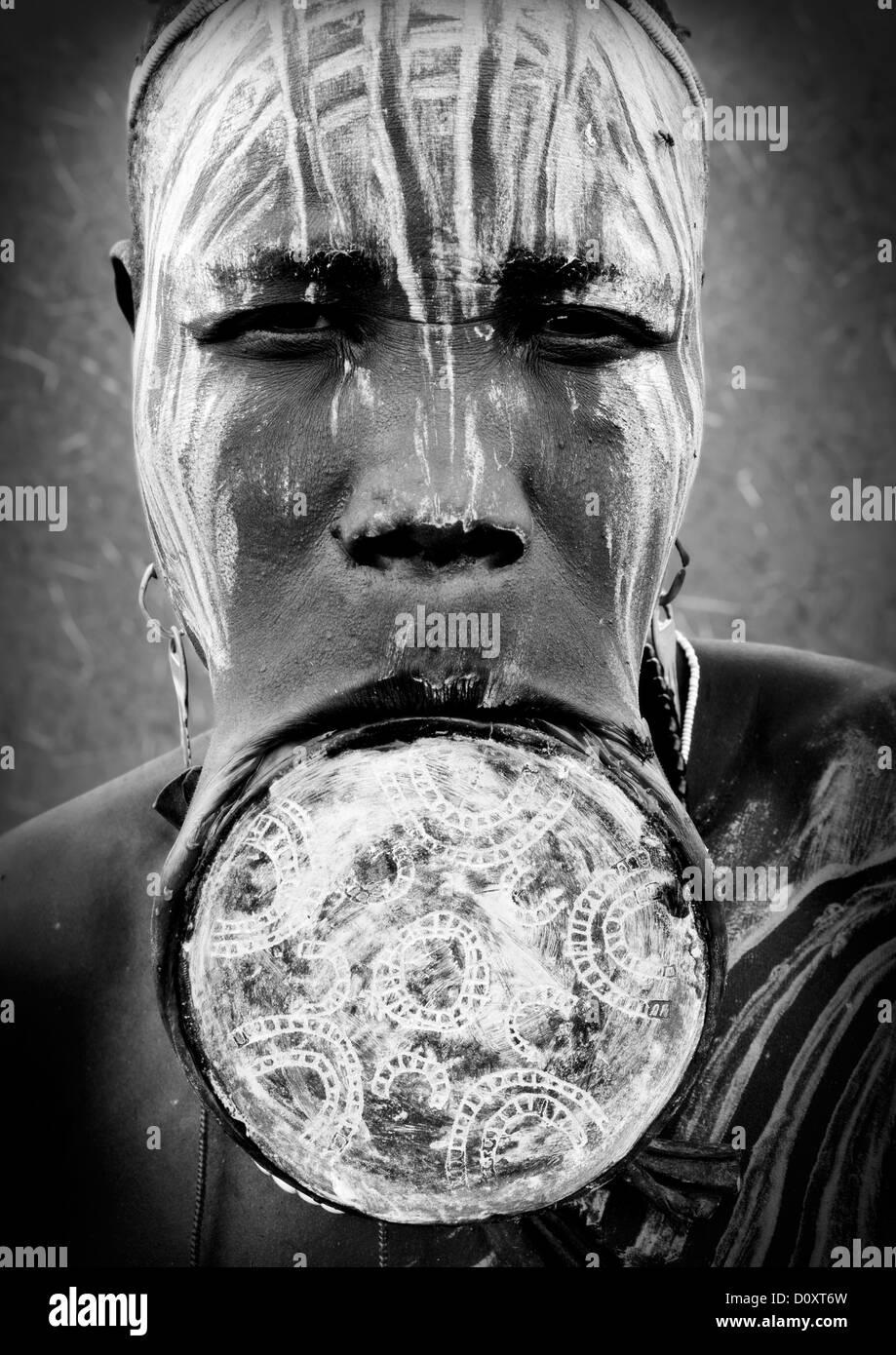 Portrait noir et blanc d'une femme de la tribu Mursi avec la lèvre plate et élargie dans les oreilles Photo Stock