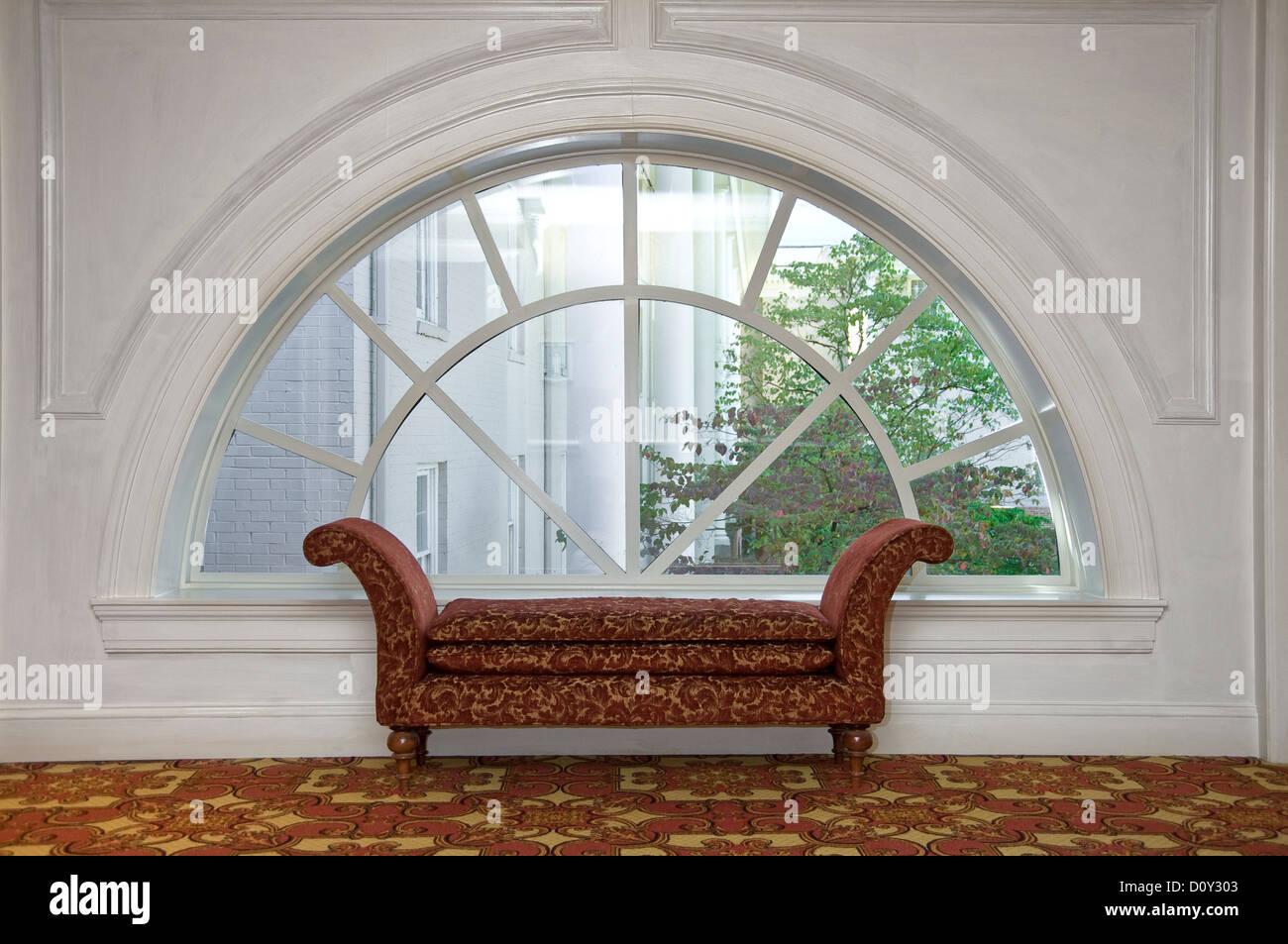 Chaise longue Chaise longue en face de Arch Fenêtre, hall de l'hôtel Photo Stock