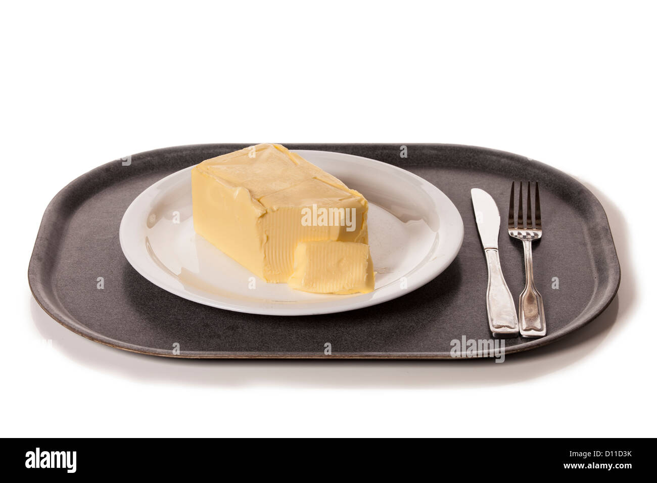 Bloc de beurre sur une assiette, le temps de manger un dîner malsaine. Photo Stock