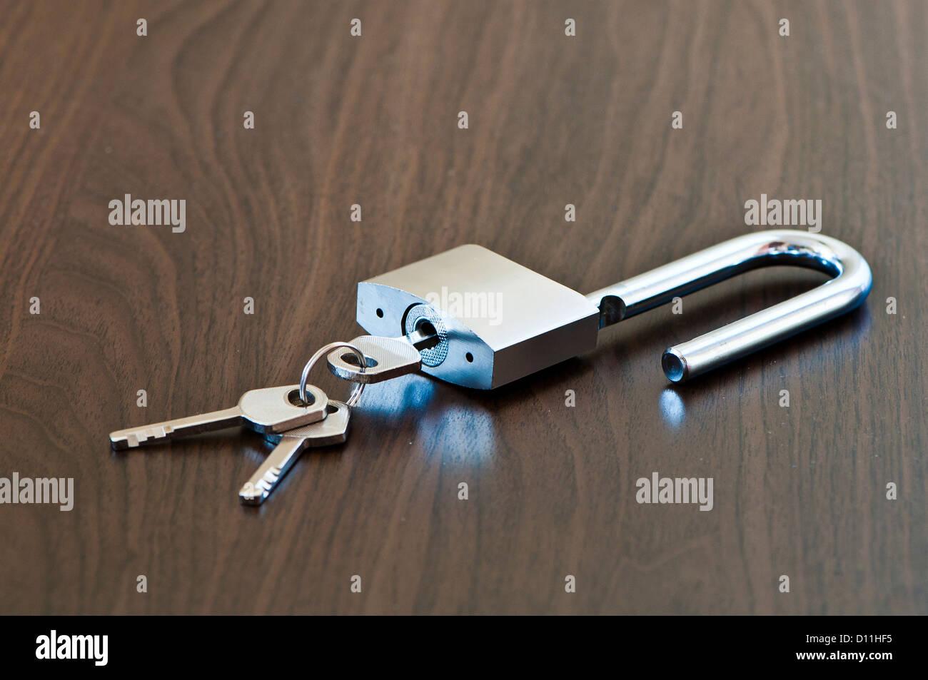 Un cadenas ouvert et la clé sur la table marron Photo Stock