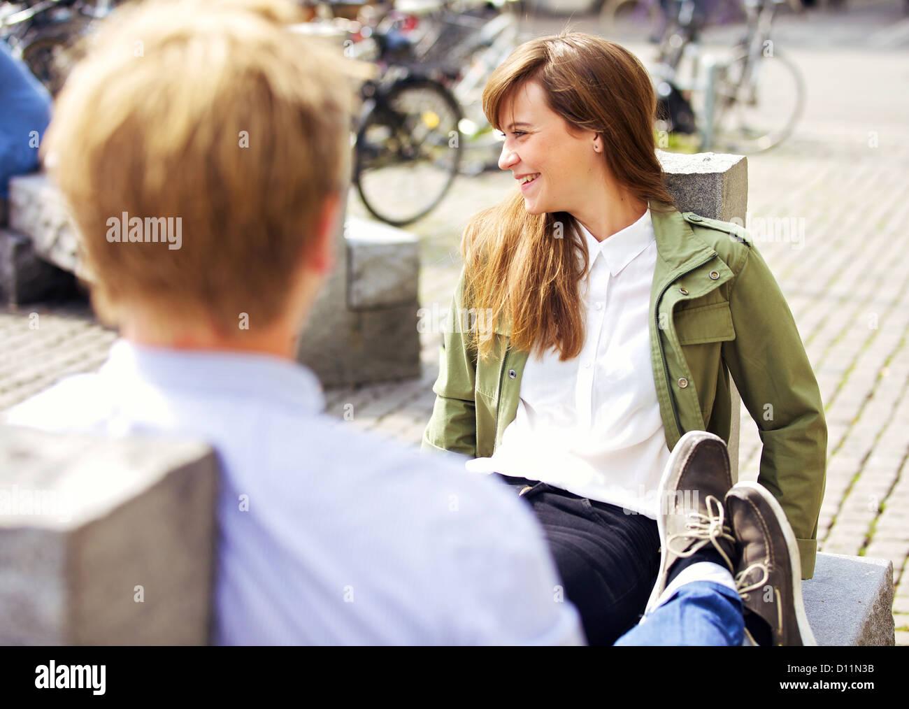 Détente attrayant femme assise sur un banc de parc avec son petit ami profiter de l'agréable matinée Photo Stock
