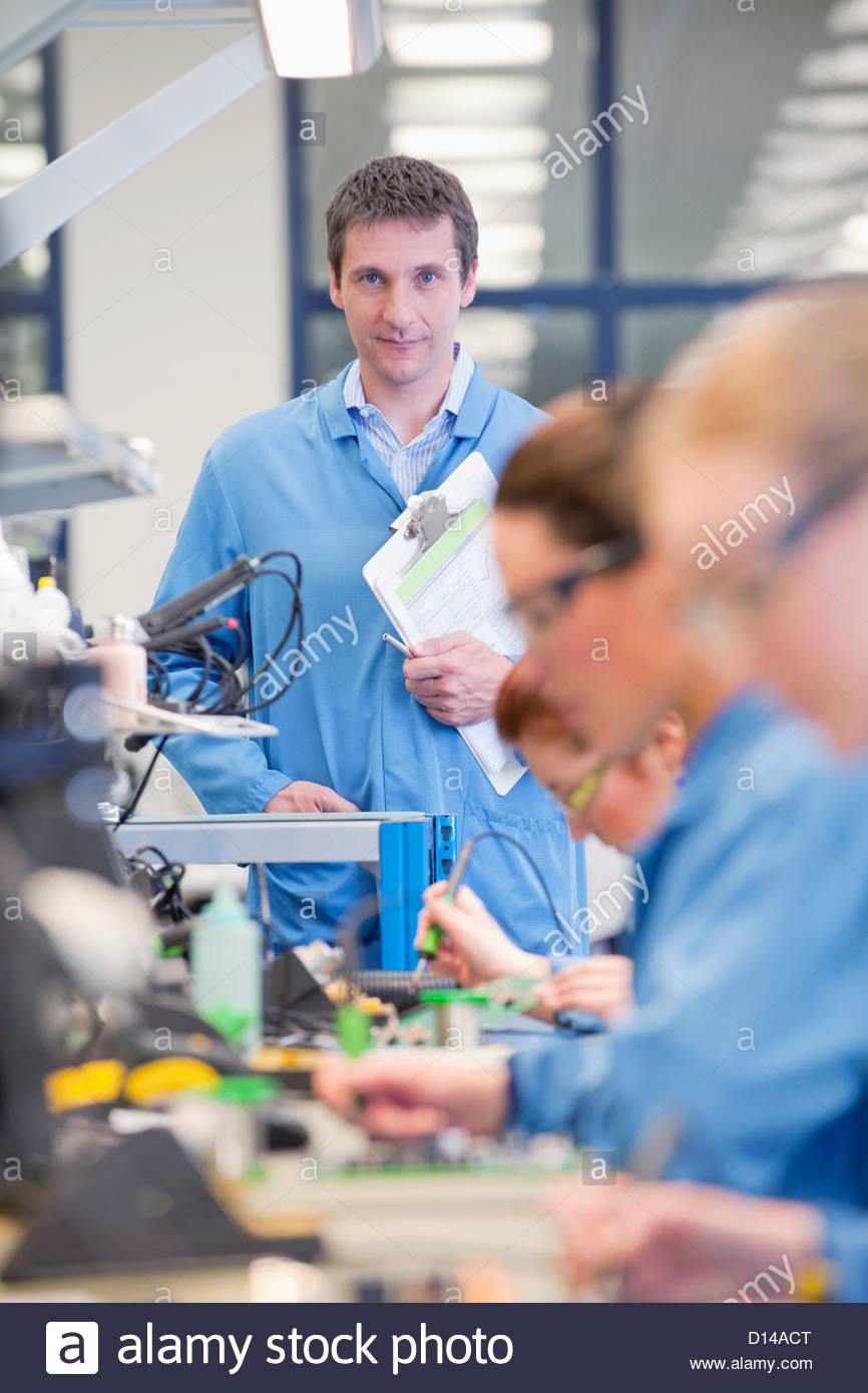 Portrait of smiling superviseur des techniciens à regarder les cartes de circuit à souder sur la ligne Photo Stock