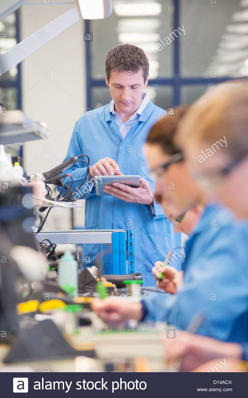 Superviseur avec tablette numérique à ligne de production dans l'usine de fabrication de circuits Photo Stock