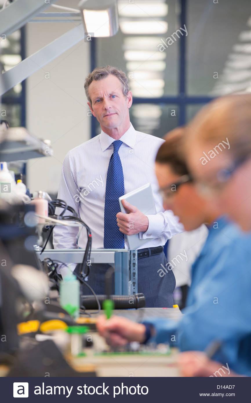 Portrait of businessman with digital tablet at ligne de production dans l'usine de fabrication de circuits imprimés Photo Stock